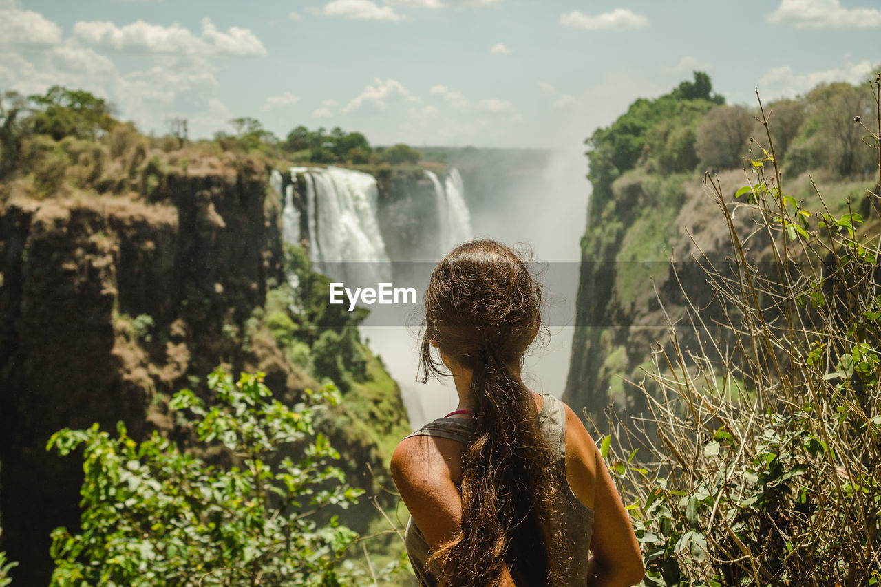 Rear view of woman looking at waterfall