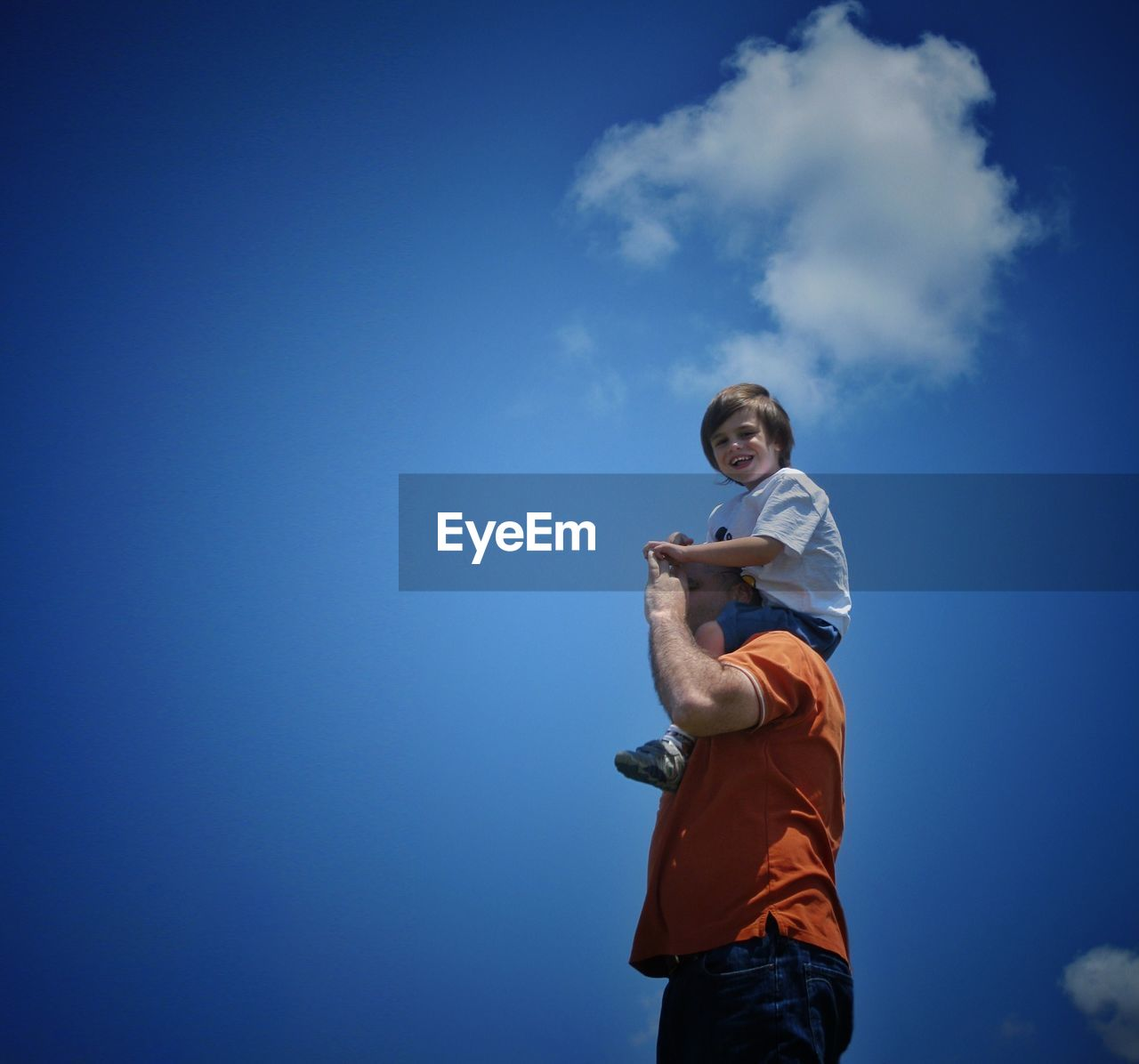 Low Angle View Of Father Carrying Son On Shoulders Against Sky