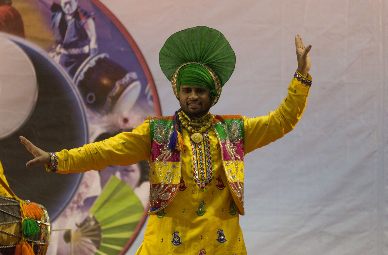 traditional clothing, real people, front view, arms raised, one person, holding, performance, standing, lifestyles, looking at camera, arts culture and entertainment, men, skill, young adult, day, portrait, happiness, playing, smiling, traditional dancing, outdoors, turban, musician, adult, people