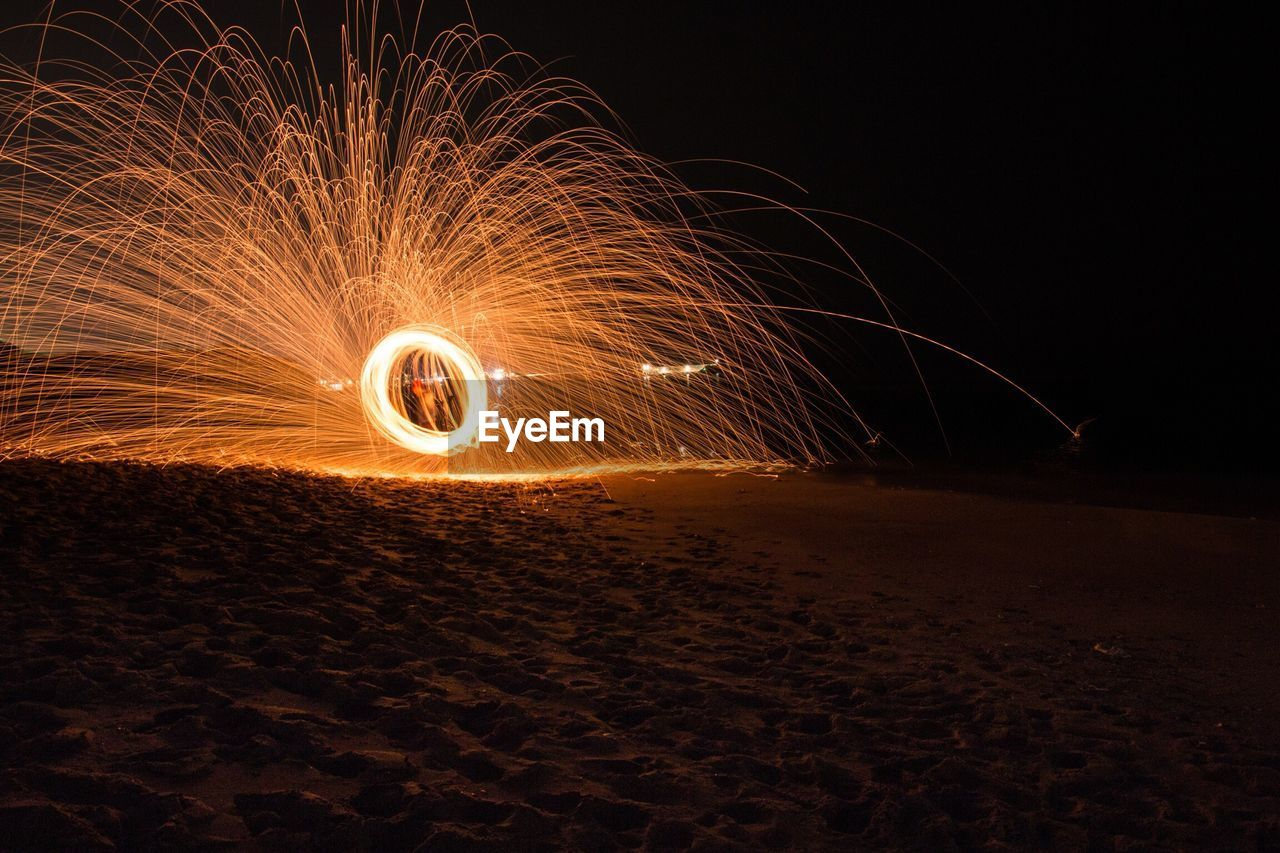 Illuminated wire wool at beach during night