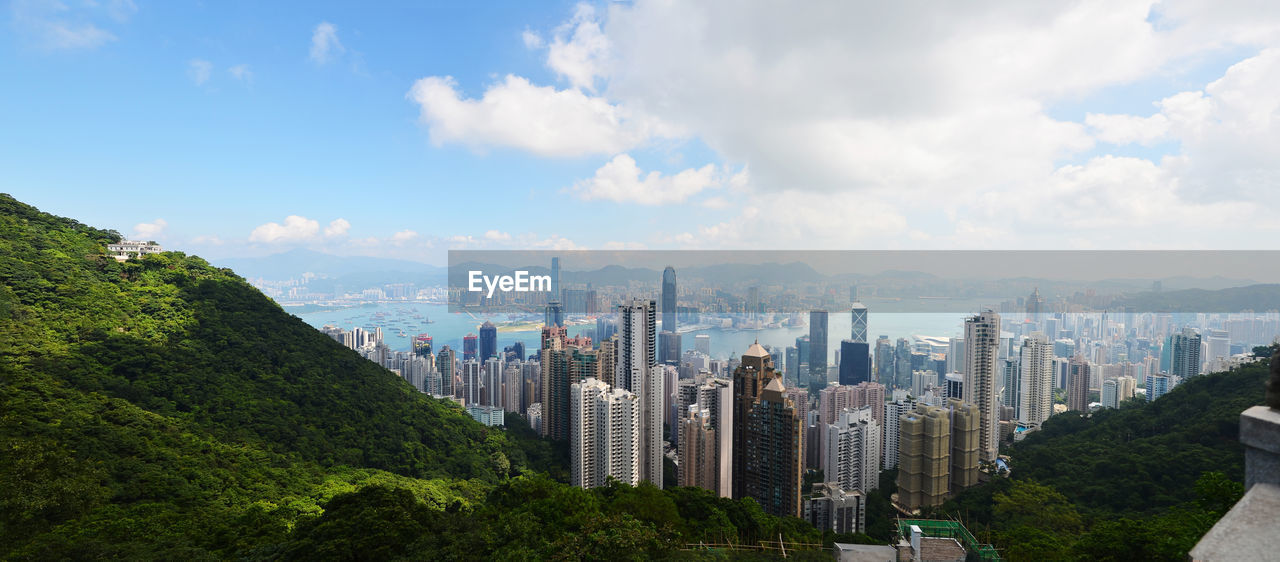 sky, city, architecture, cloud - sky, building exterior, built structure, tree, building, nature, cityscape, plant, landscape, residential district, no people, office building exterior, tall - high, urban skyline, day, skyscraper, mountain, outdoors, modern, financial district