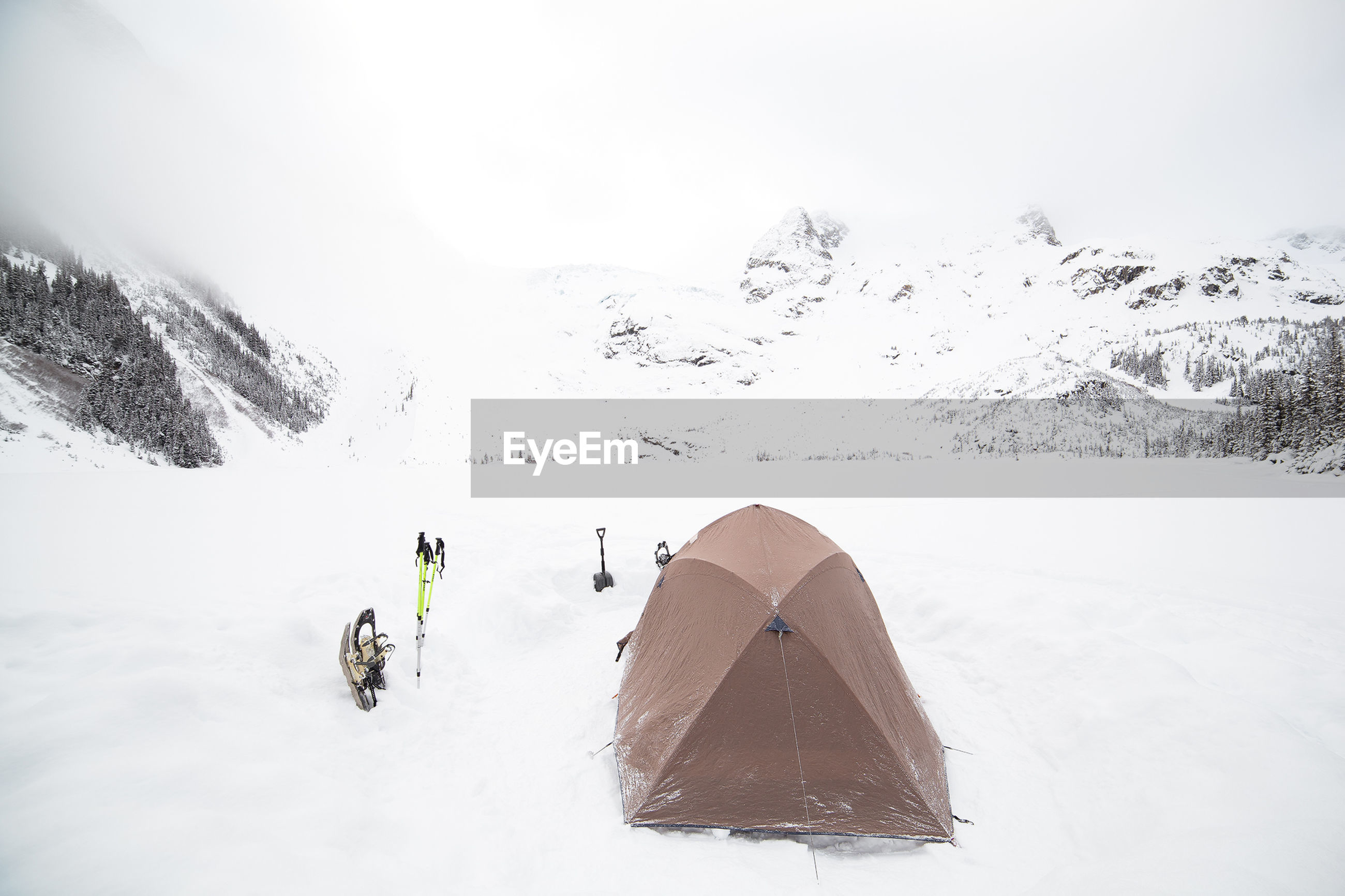 Tent on snow covered field against mountains