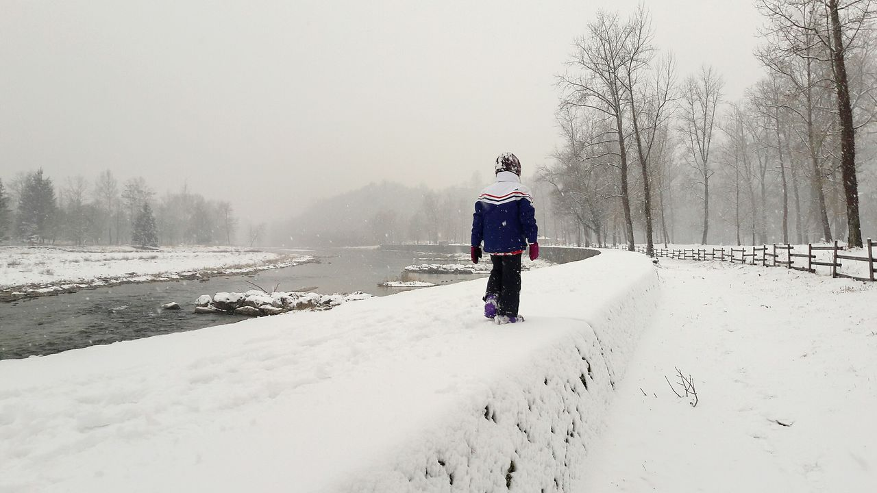 Rear View Of Boy On Snow Covered Landscape