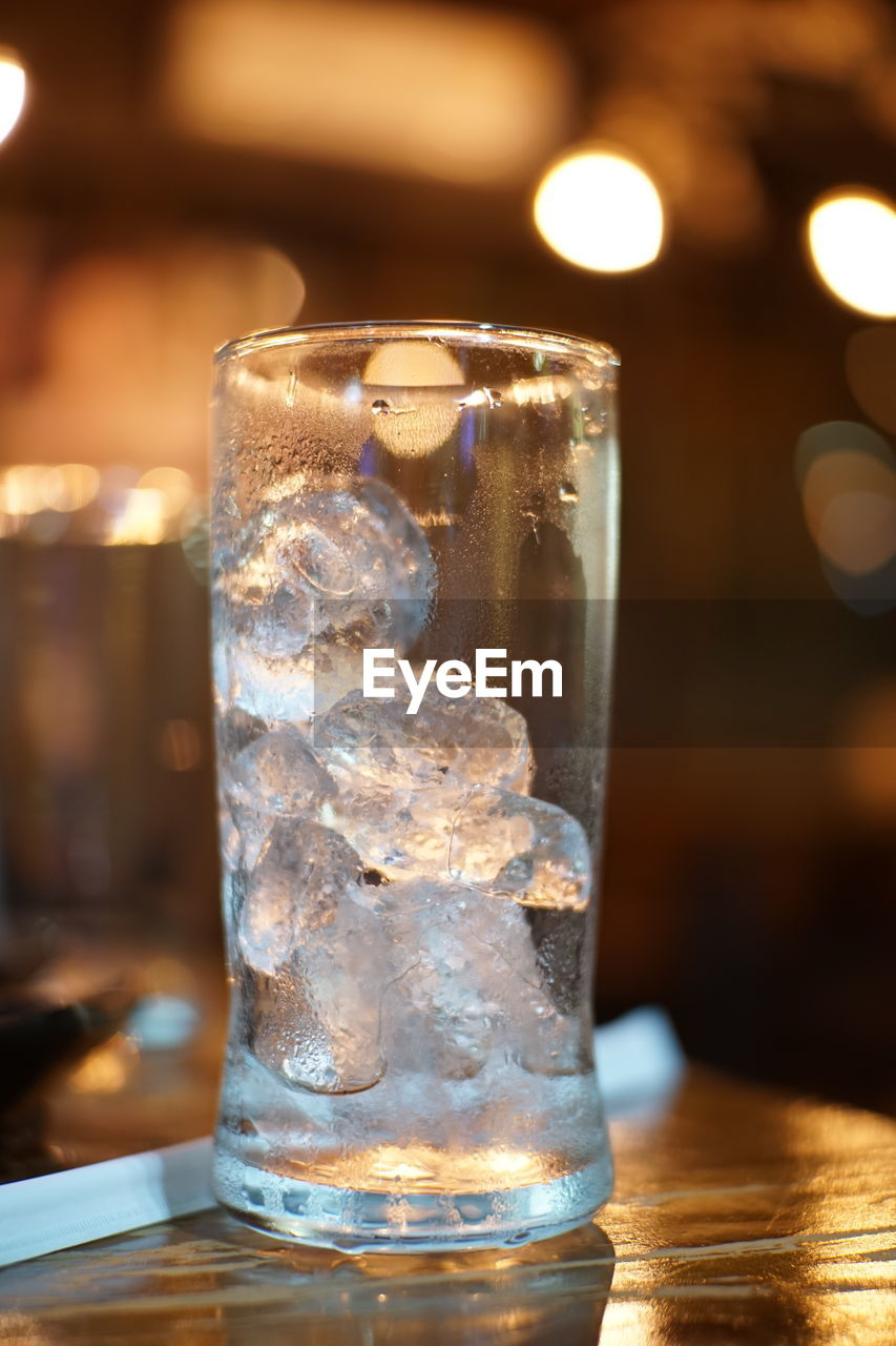 table, focus on foreground, close-up, glass - material, transparent, indoors, cold temperature, no people, refreshment, food and drink, drink, ice, still life, glass, drinking glass, illuminated, ice cube, frozen, household equipment, freshness, melting, purity, bar counter