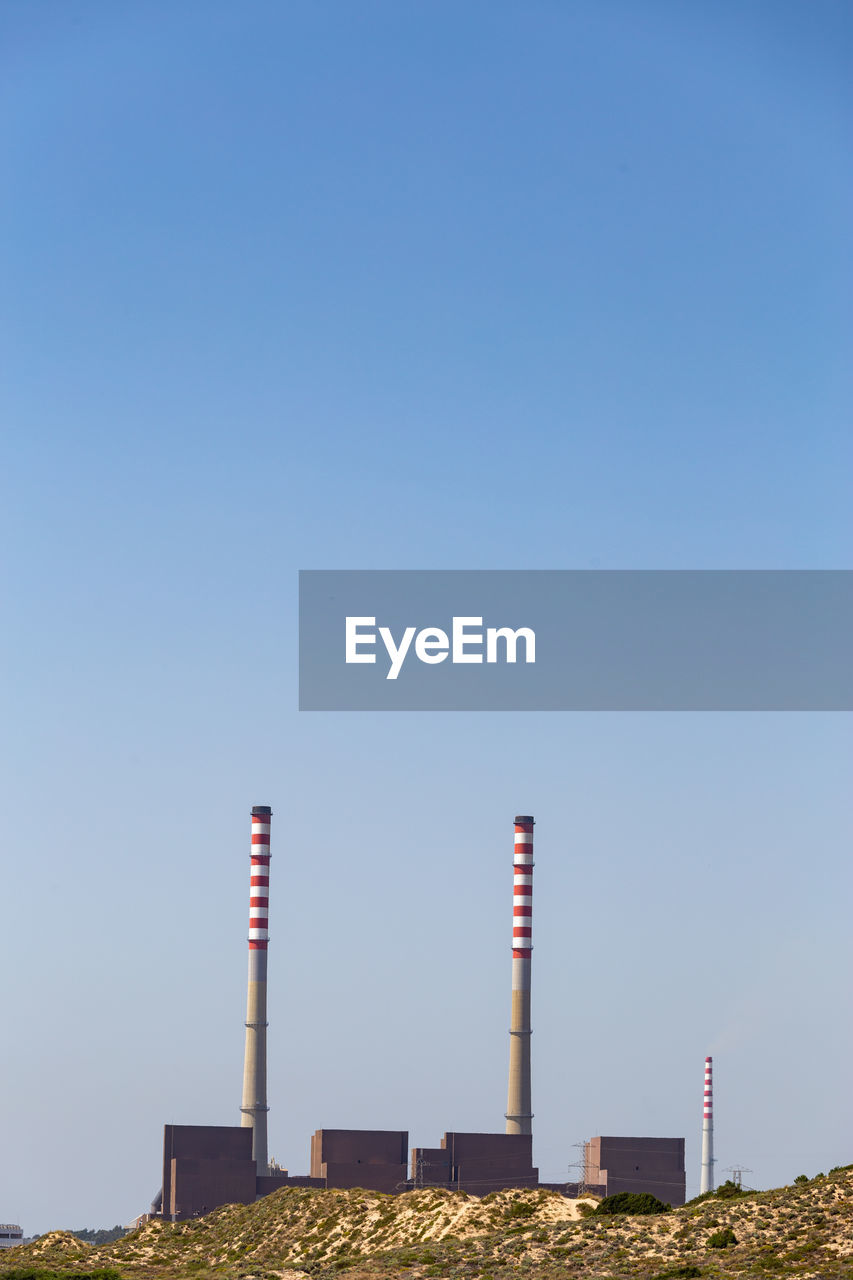 LOW ANGLE VIEW OF SMOKE STACK AGAINST CLEAR SKY