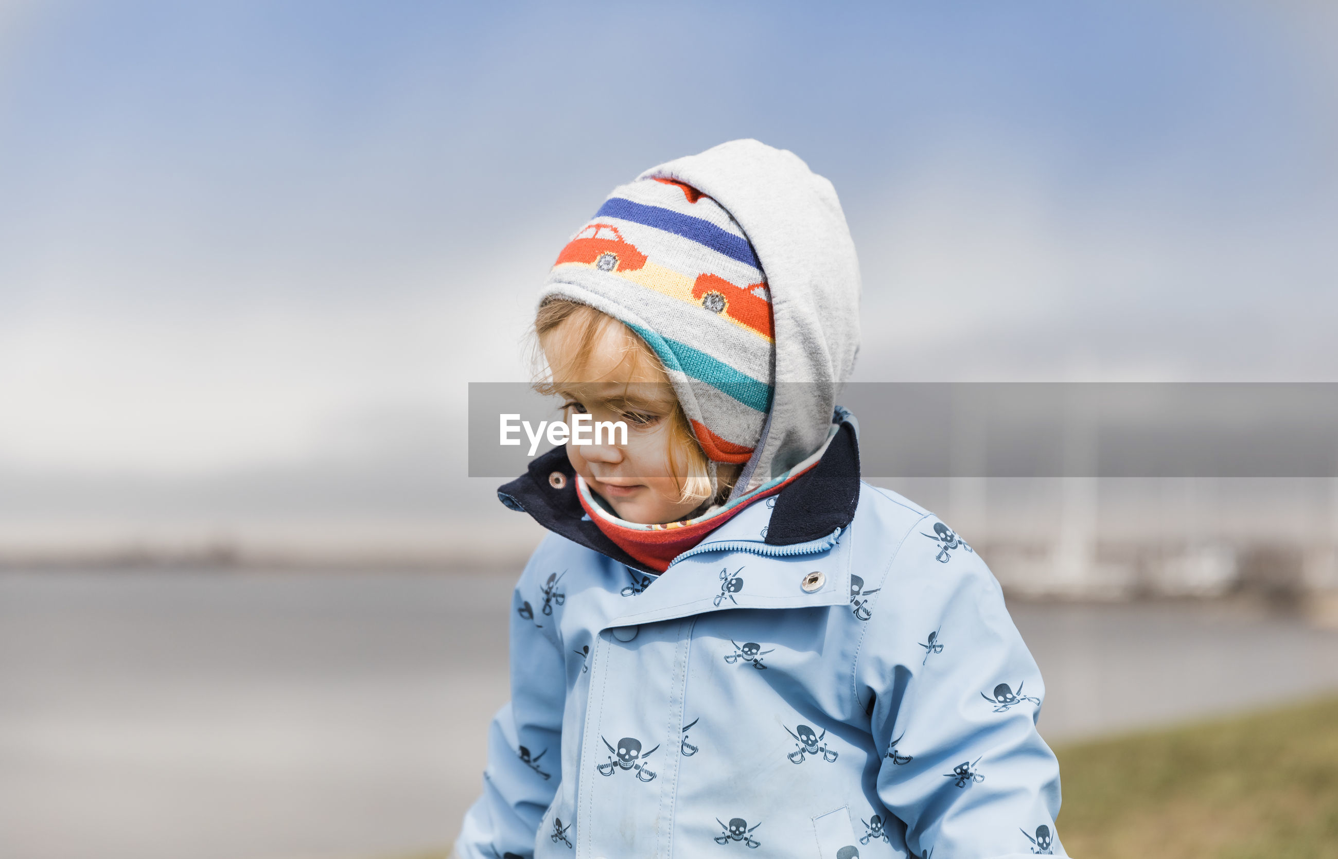 Close-up of girl wearing warm clothes while standing against sky during winter