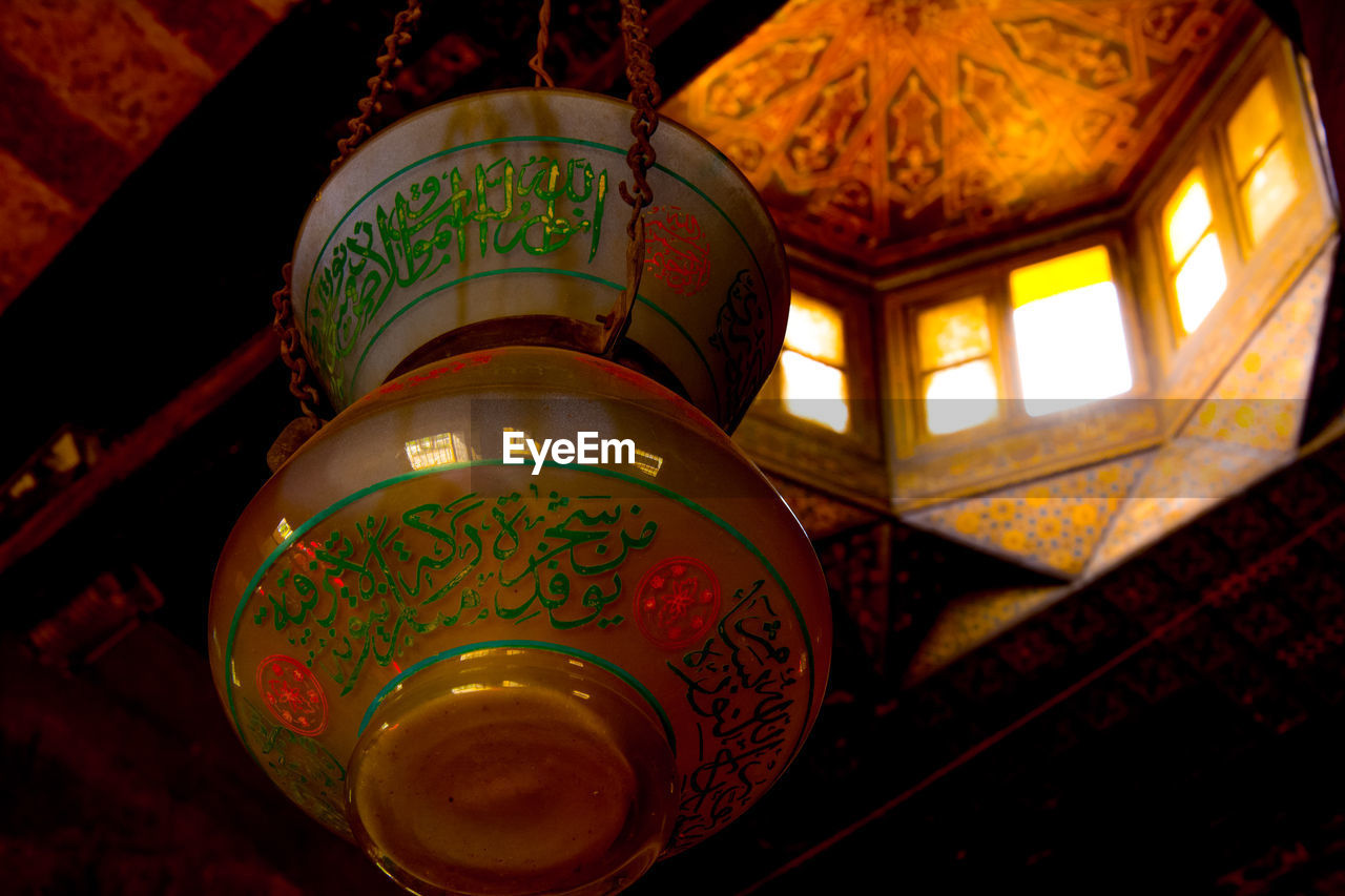 lighting equipment, indoors, illuminated, no people, pattern, low angle view, lantern, close-up, design, electric lamp, script, non-western script, focus on foreground, ceiling, hanging, decoration, text, spirituality, light, floral pattern, crockery, paper lantern, ornate