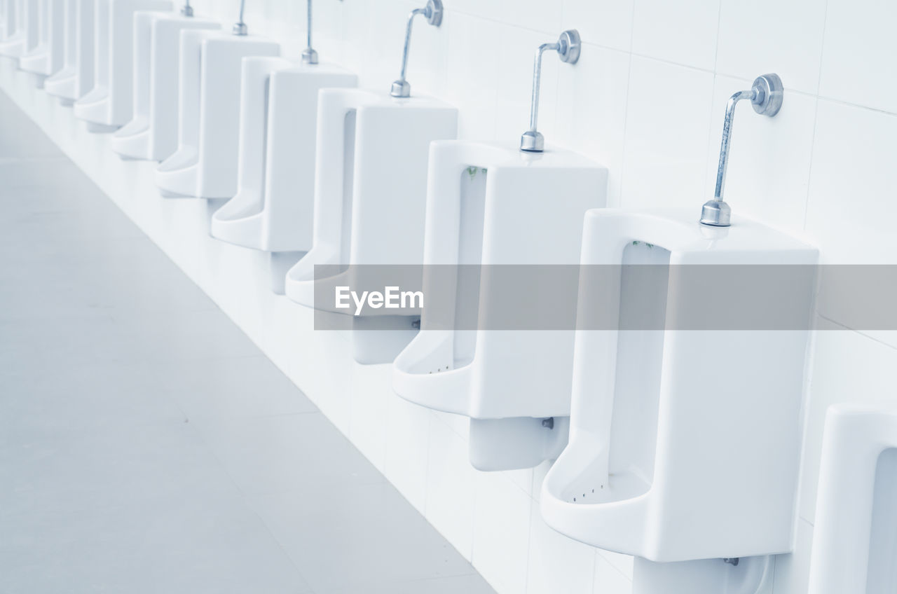 bathroom, white color, in a row, no people, indoors, flooring, urinal, toilet, domestic room, hygiene, empty, absence, tile, repetition, home, public building, public restroom, wall - building feature, seat, architecture, clean