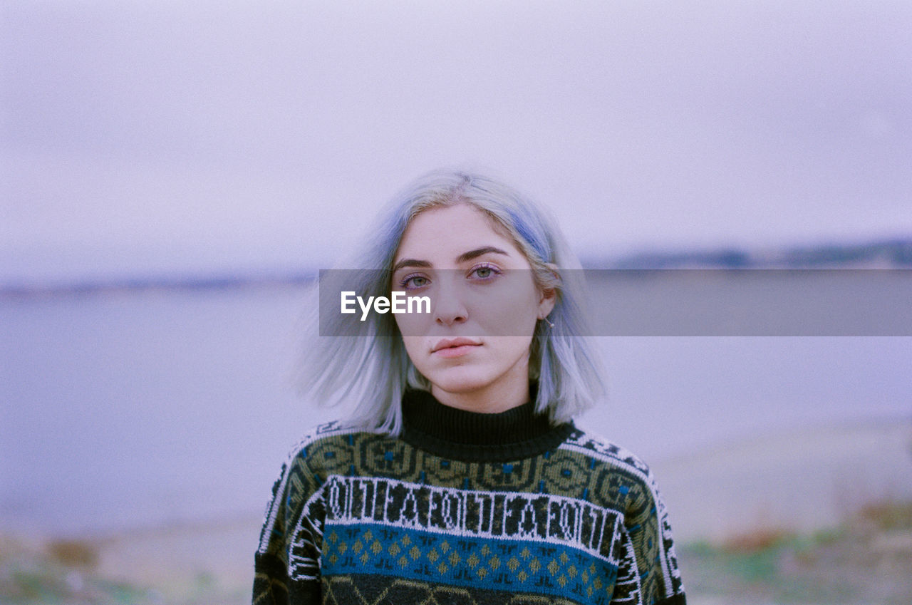 Portrait Of Beautiful Woman With Dyed Hair Standing Against Lake