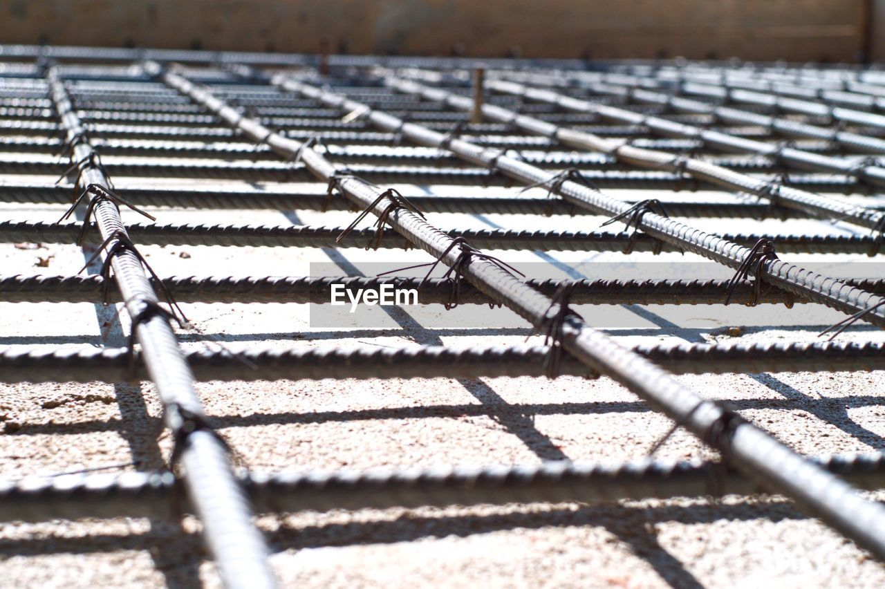 metal, no people, pattern, sunlight, day, in a row, nature, close-up, outdoors, selective focus, repetition, security, shadow, focus on foreground, large group of objects, backgrounds, safety, abundance, protection, architecture, concrete, roof tile