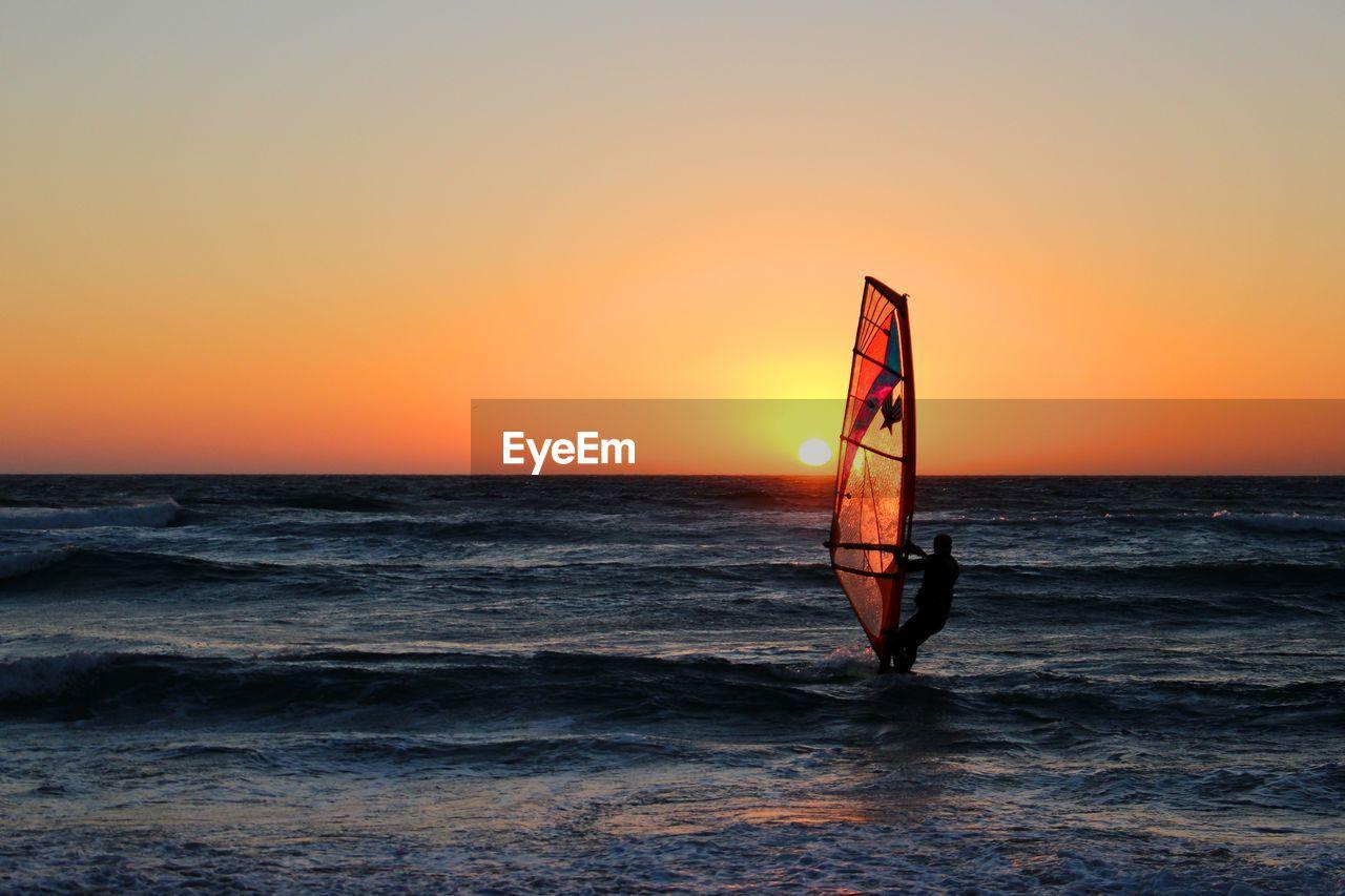 Silhouette Man Windsurfing On Sea Against Orange Sky