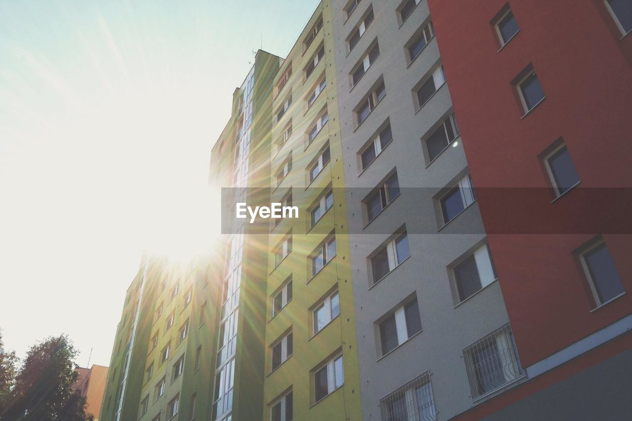 building exterior, window, architecture, sunlight, low angle view, built structure, day, no people, sky, apartment, outdoors, clear sky