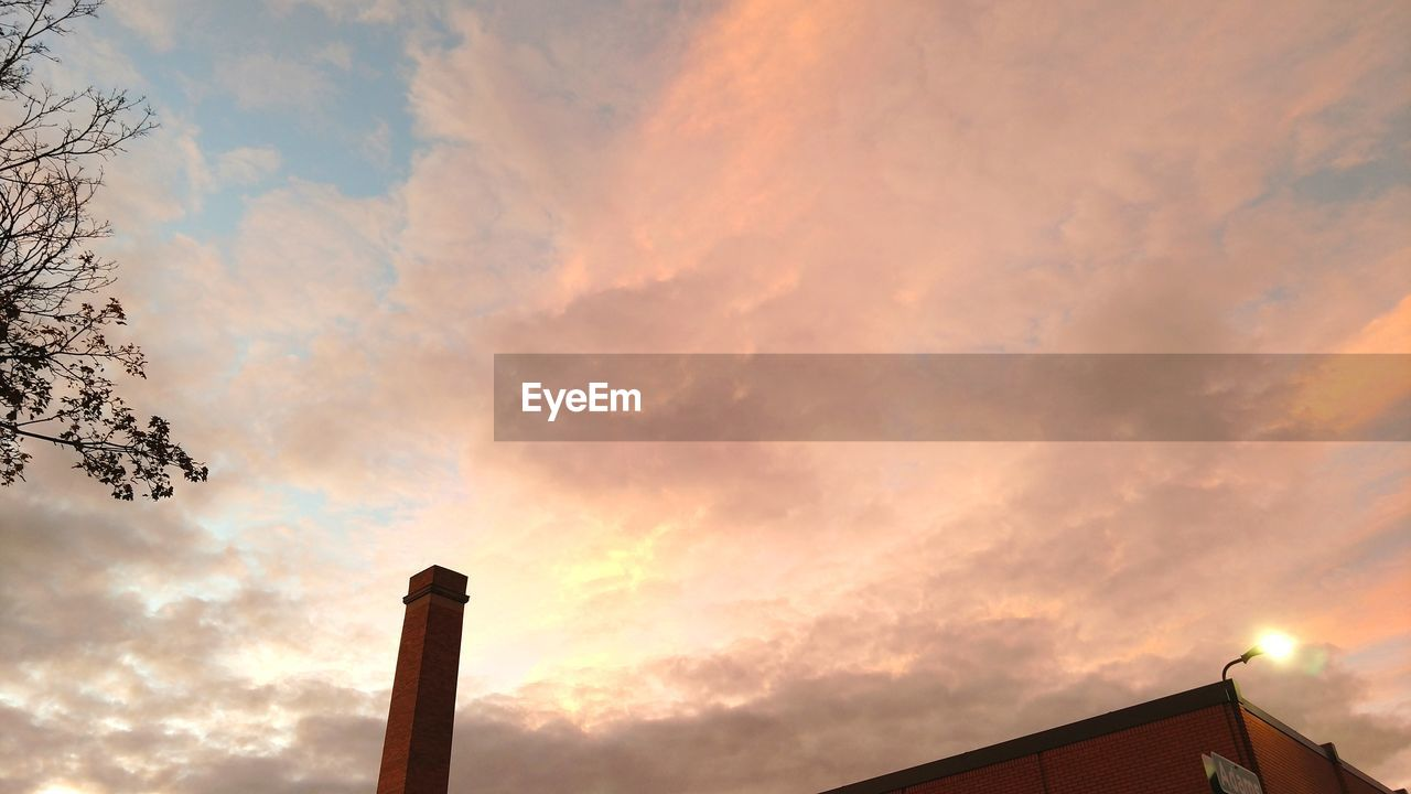 cloud - sky, sky, low angle view, architecture, built structure, building exterior, sunset, nature, no people, orange color, industry, outdoors, beauty in nature, factory, smoke stack, silhouette, building, chimney, environmental issues, scenics - nature, pollution