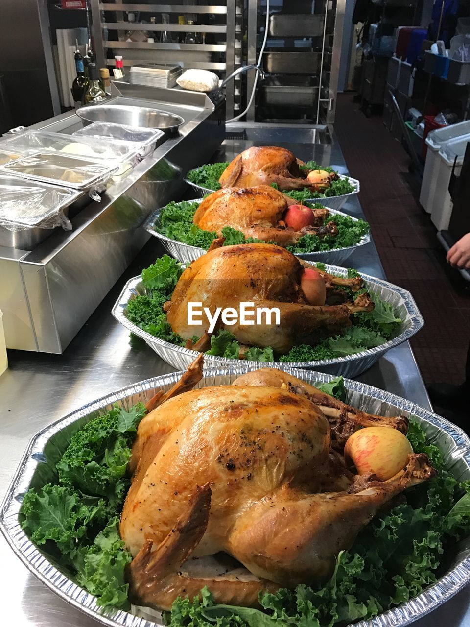 High angle view of roasted chickens in plates with lettuce and apples on kitchen counter at restaurant