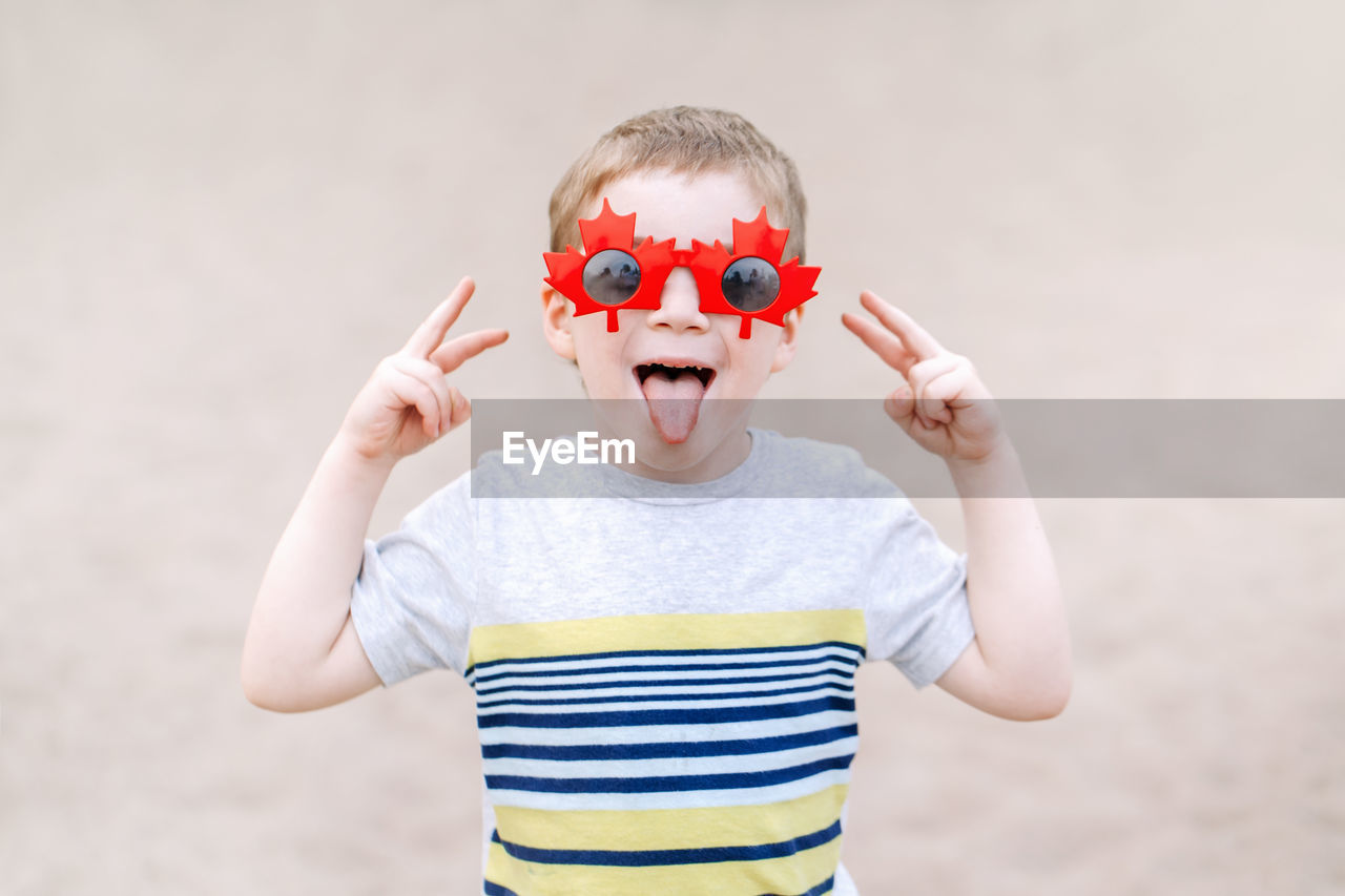 Portrait of cute boy gesturing while wearing sunglasses