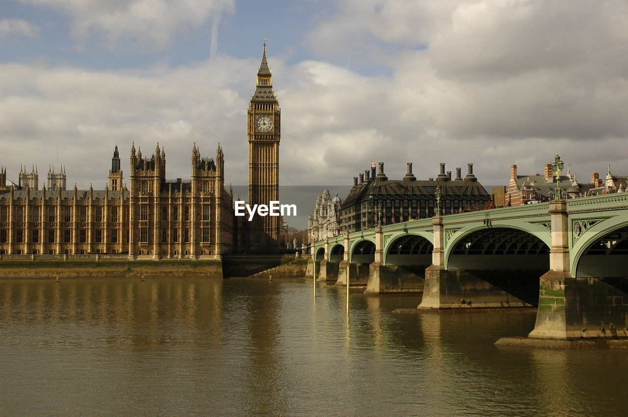 Westminster Bridge Over Thames River By Big Ben Against Cloudy Sky