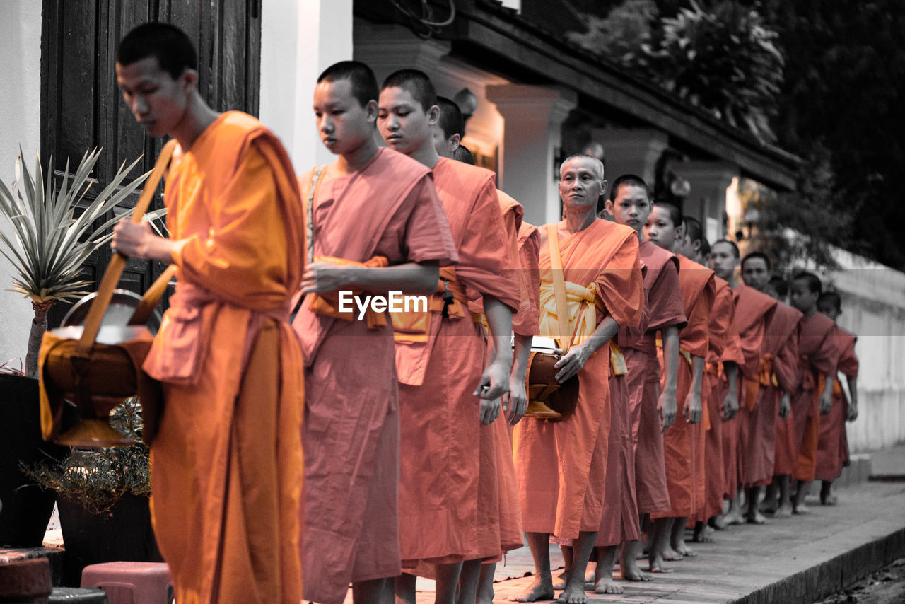 orange color, traditional clothing, religion, standing, men, real people, day, outdoors, only men, adult, people, adults only
