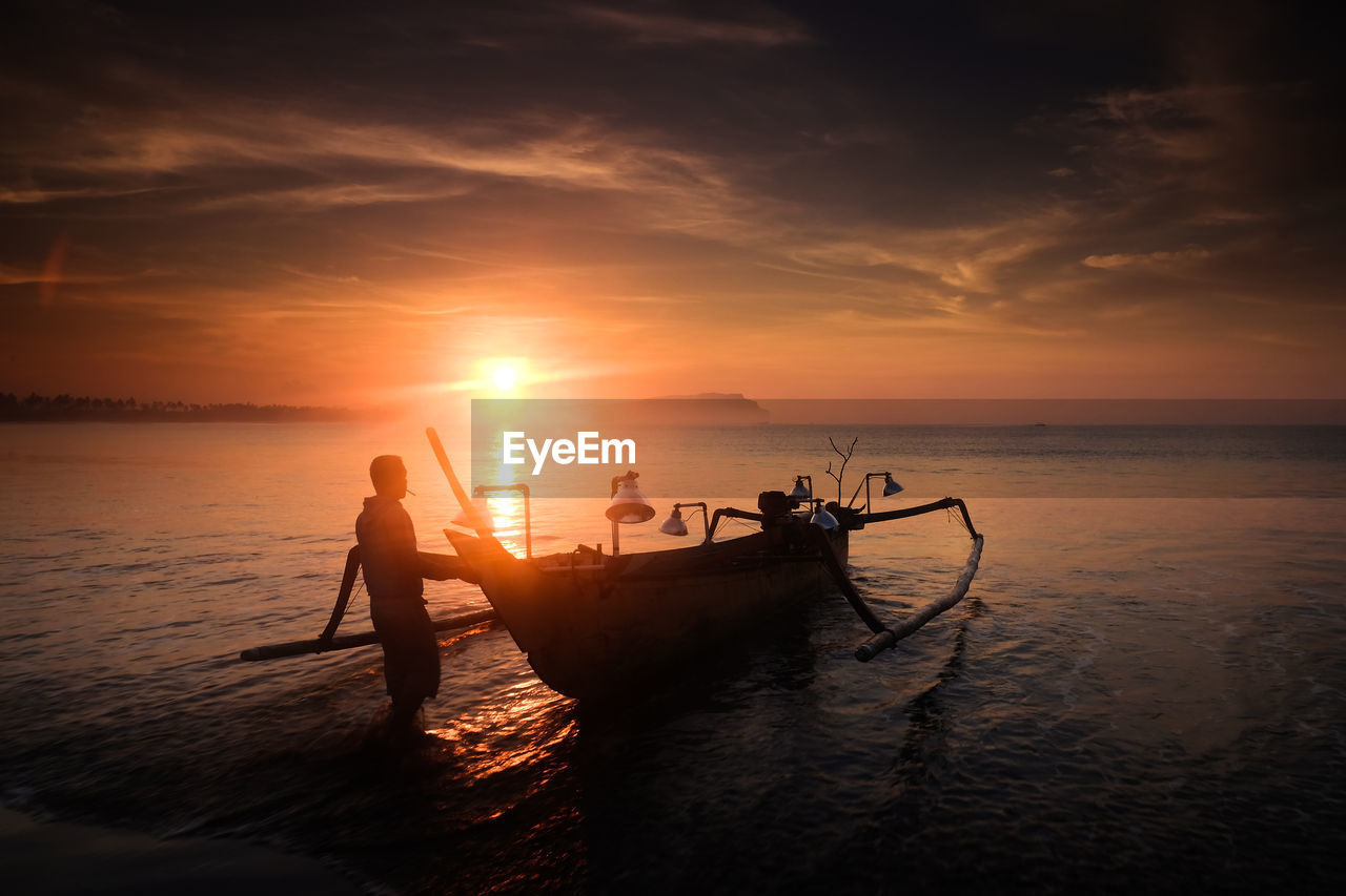 Silhouette fisherman with boat in sea against sky during sunset