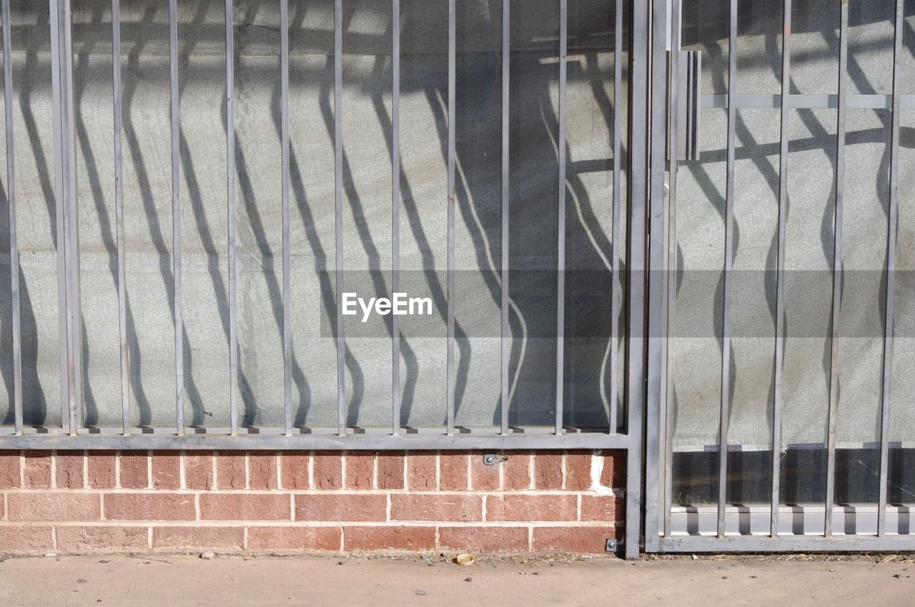 no people, metal, architecture, built structure, day, building exterior, pattern, wall - building feature, glass - material, window, side by side, outdoors, wall, railing, brick wall, security, brick, close-up, transparent, nature