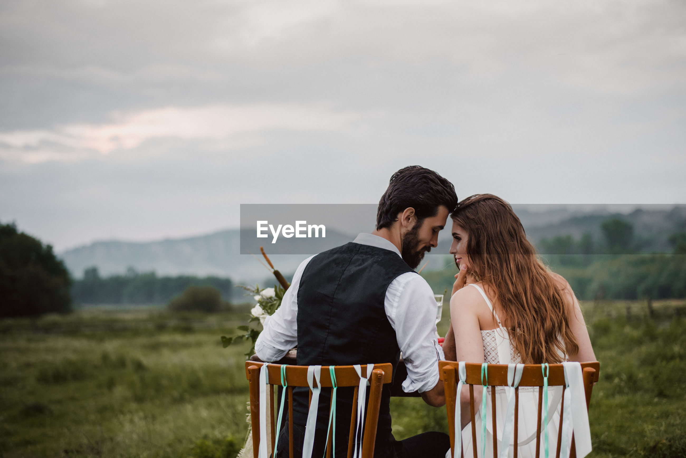 Rear view of bride and bridegroom sitting on chairs at field