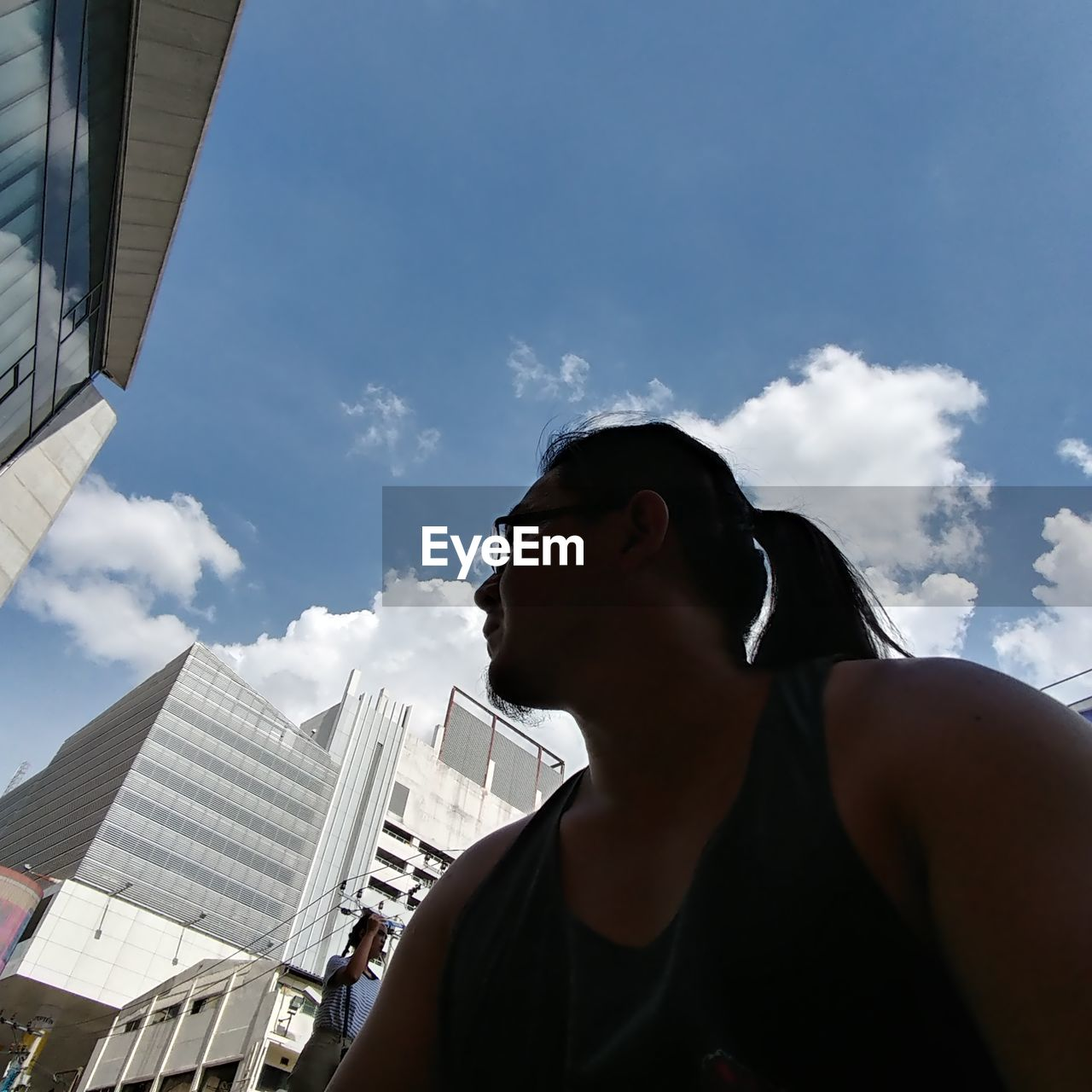 sky, architecture, building exterior, built structure, real people, cloud - sky, day, outdoors, city, one person, low angle view, skyscraper, cityscape, young adult