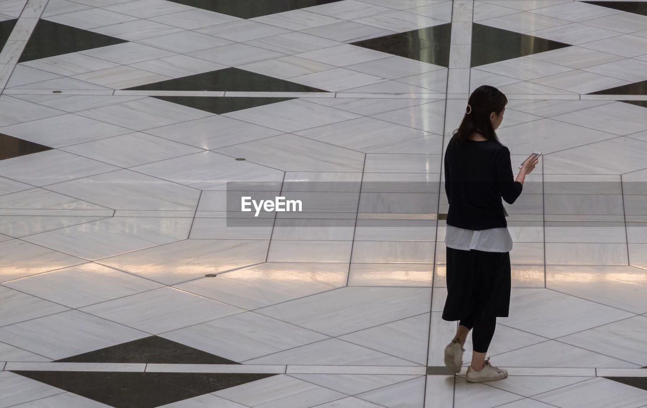 REAR VIEW OF WOMAN STANDING AGAINST TILED FLOOR