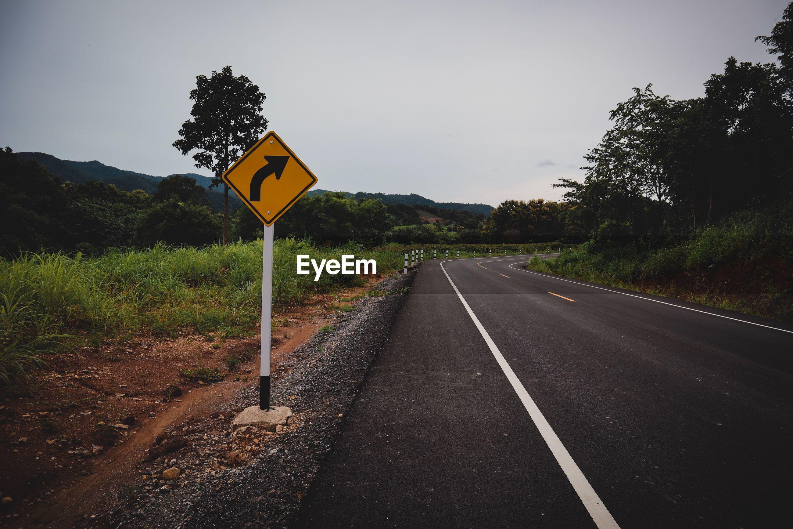 Arrow symbol by road against sky