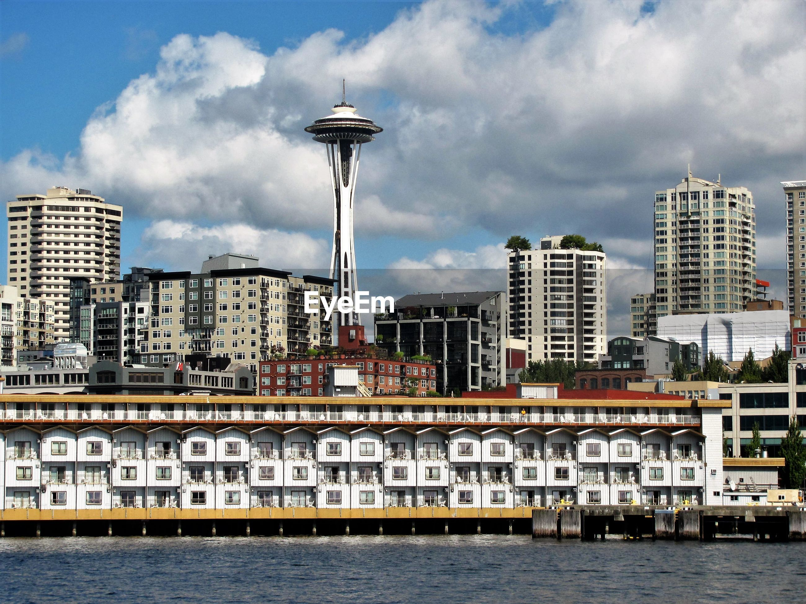 Space needle amidst buildings in front of river against cloudy sky on sunny day
