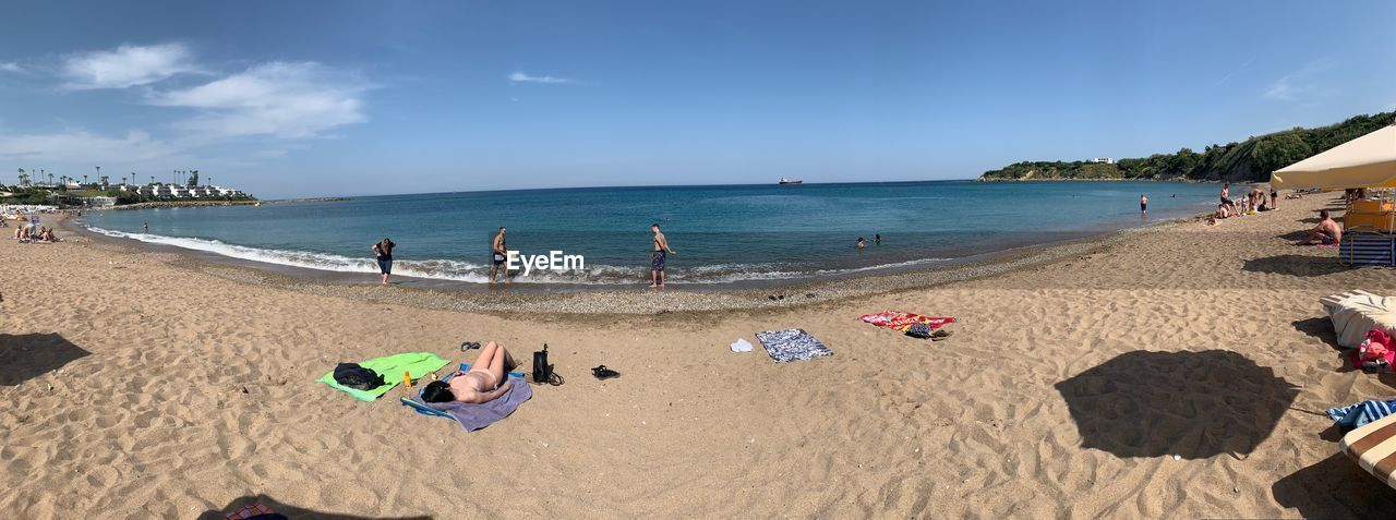 beach, land, sand, water, sea, sky, group of people, vacations, nature, scenics - nature, beauty in nature, holiday, trip, horizon, day, real people, sunlight, horizon over water, large group of people, outdoors