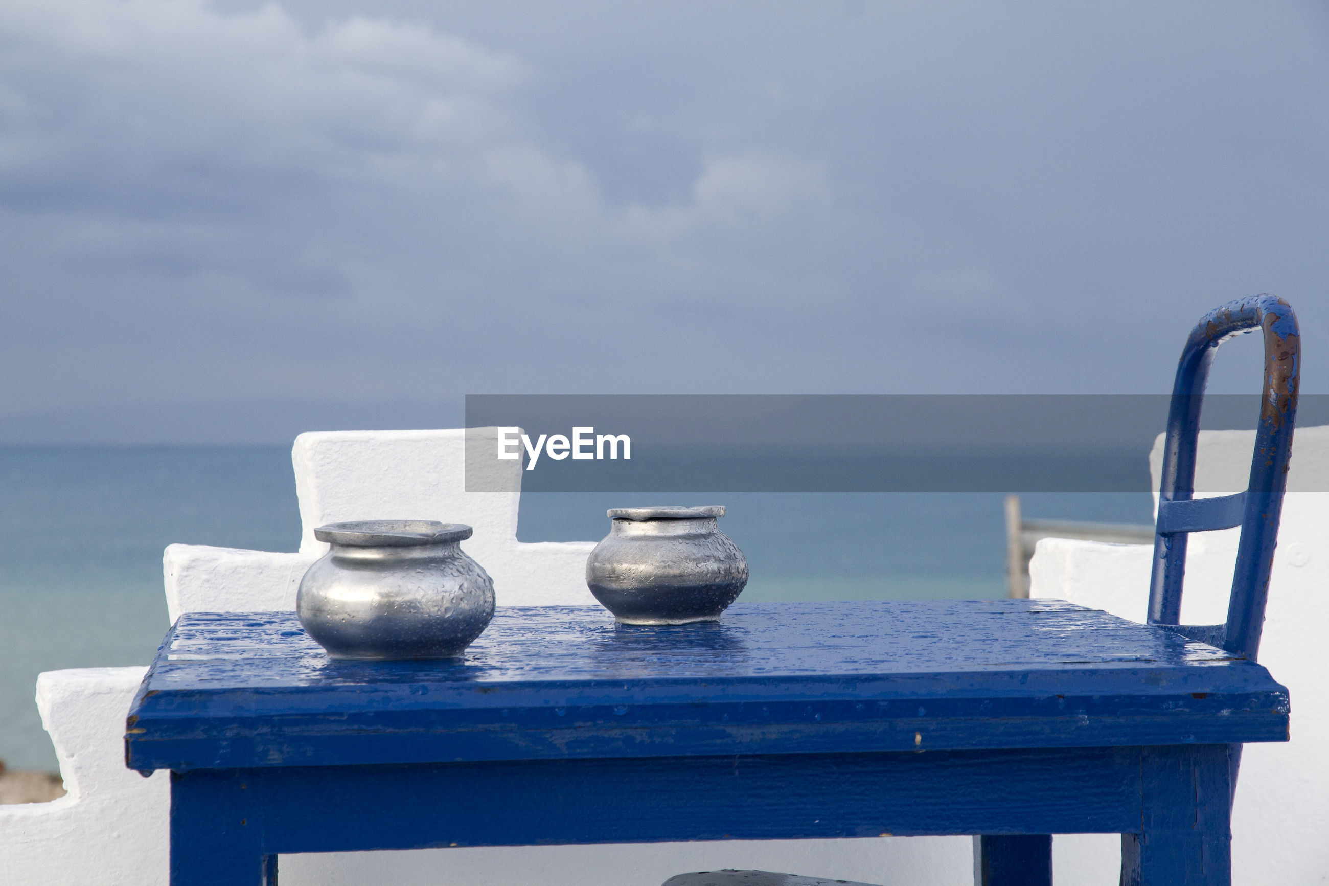 Containers on table at sea against blue sky