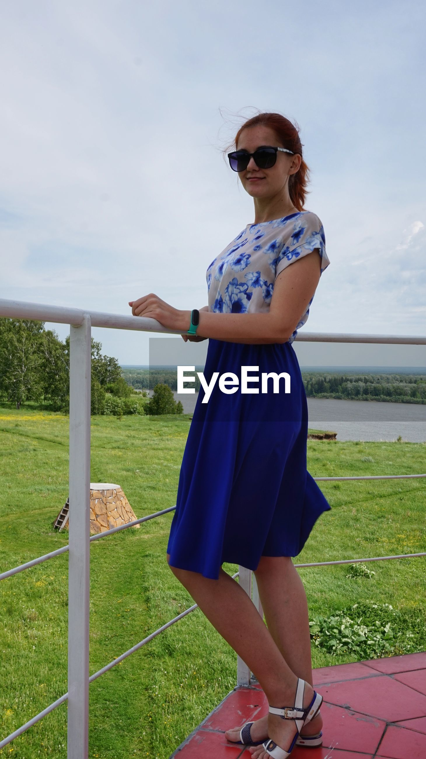 Full length portrait of young woman standing by railing on land
