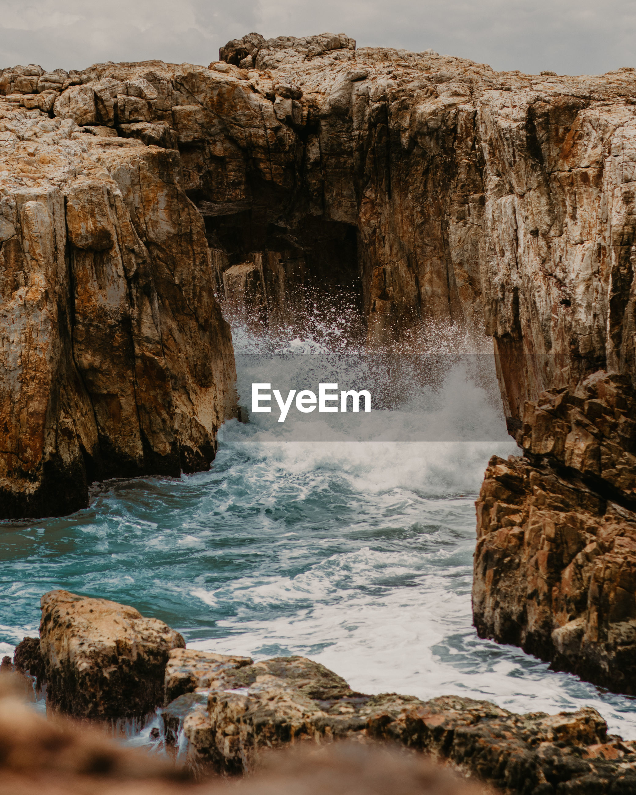 Scenic view of splashing water in sea by rock formation