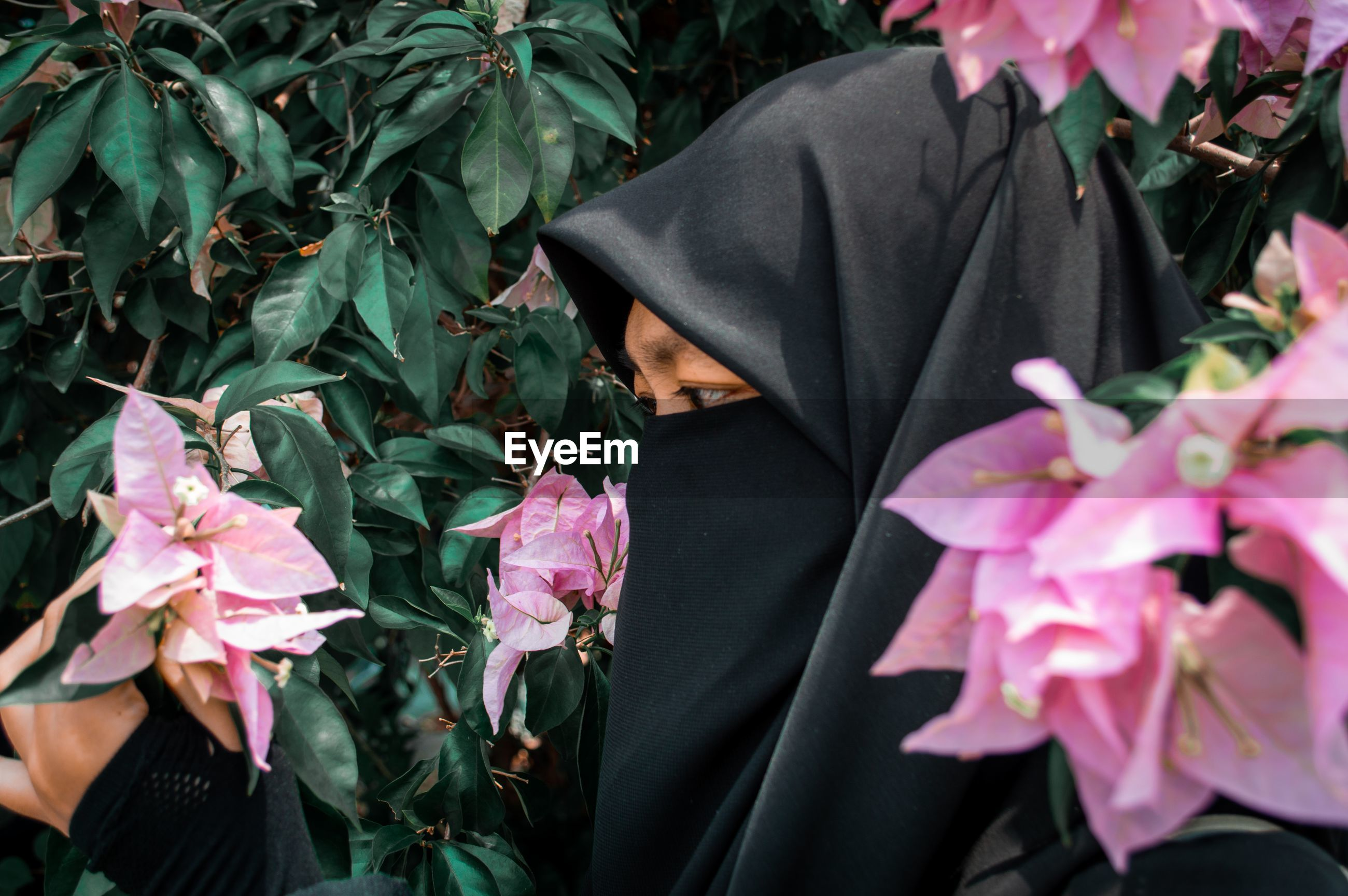 Close-up of woman in hijab amidst flowering plant