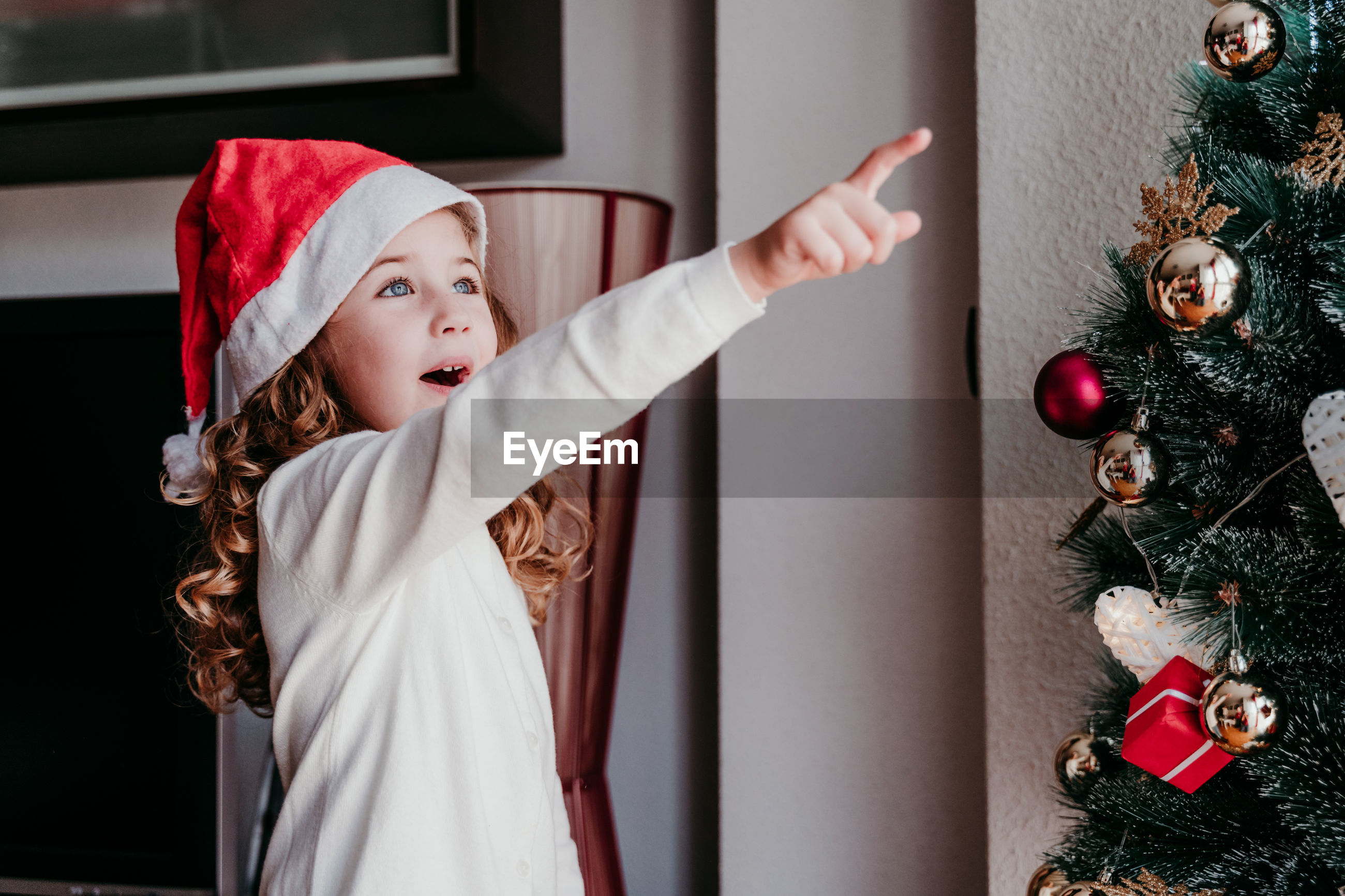 Cute girl pointing while standing by christmas tree at home