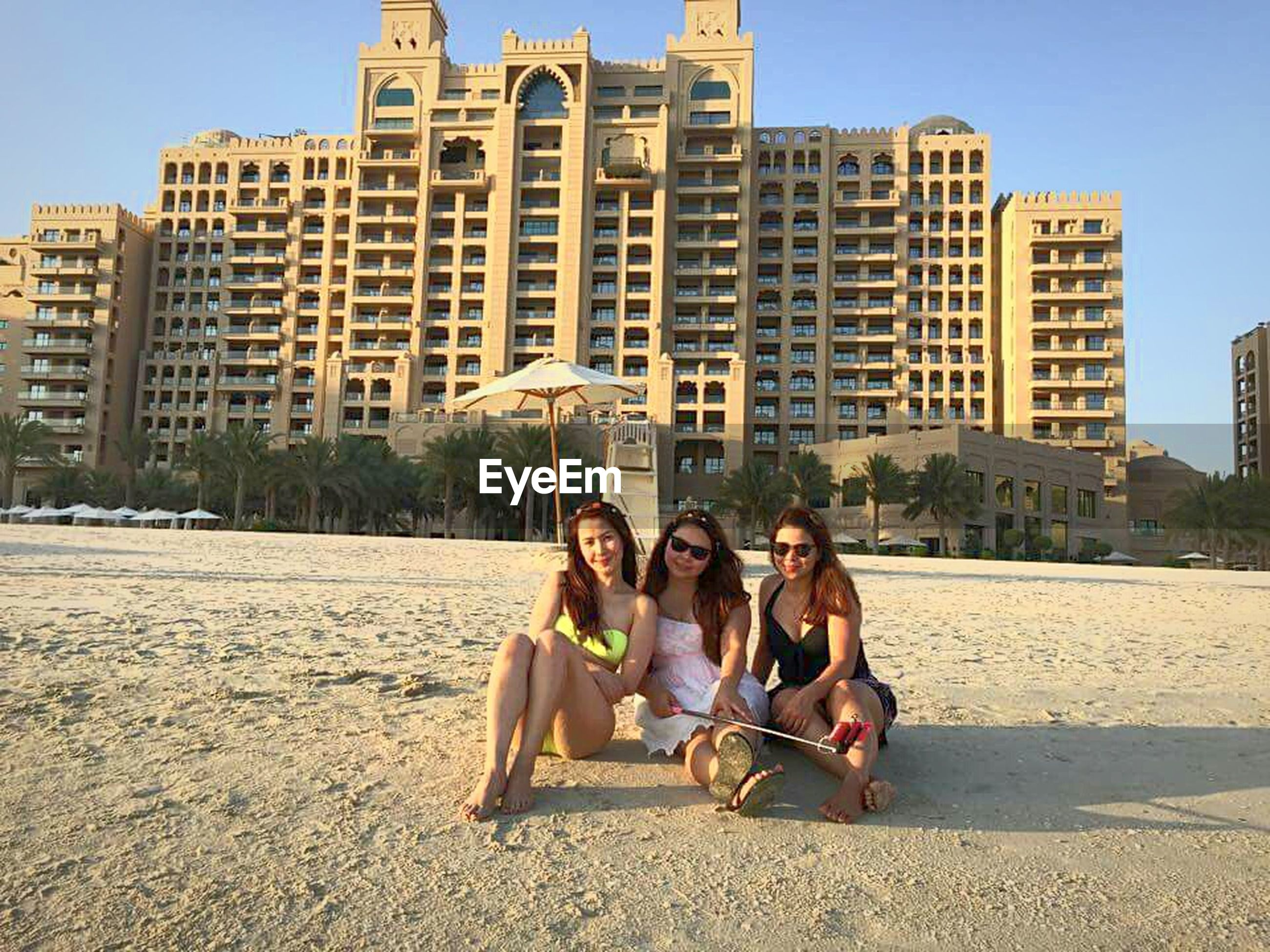 lifestyles, leisure activity, togetherness, building exterior, architecture, built structure, sitting, bonding, full length, casual clothing, relaxation, love, person, men, young adult, vacations, friendship, sunlight