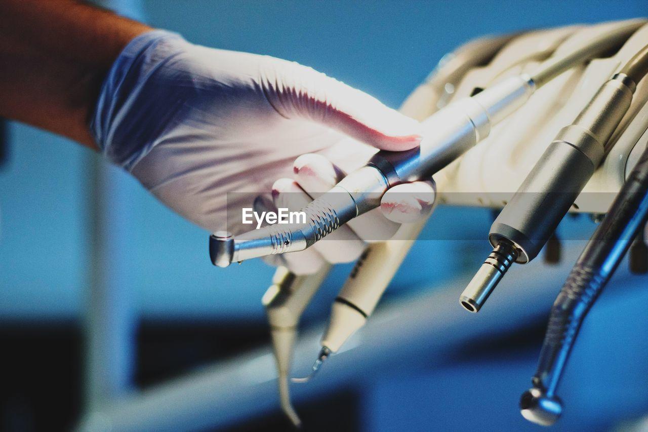 Close-up of dentist holding dental equipment