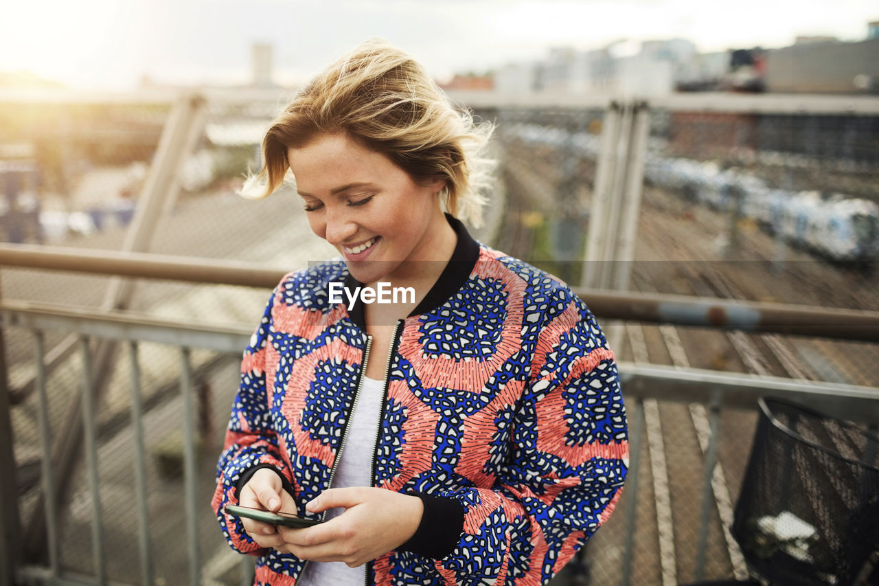 PORTRAIT OF SMILING YOUNG WOMAN HOLDING SMART PHONE
