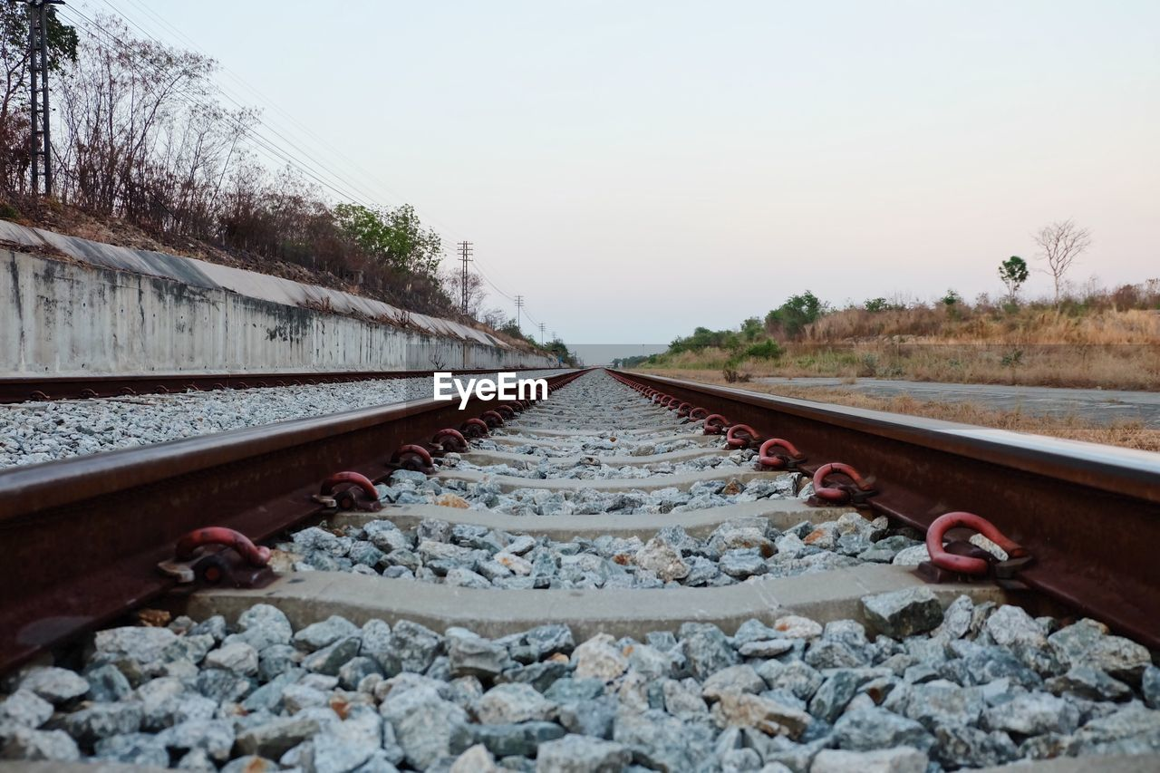 rail transportation, track, railroad track, sky, direction, the way forward, nature, plant, clear sky, tree, transportation, no people, day, diminishing perspective, metal, vanishing point, solid, outdoors, rock, surface level, gravel, long