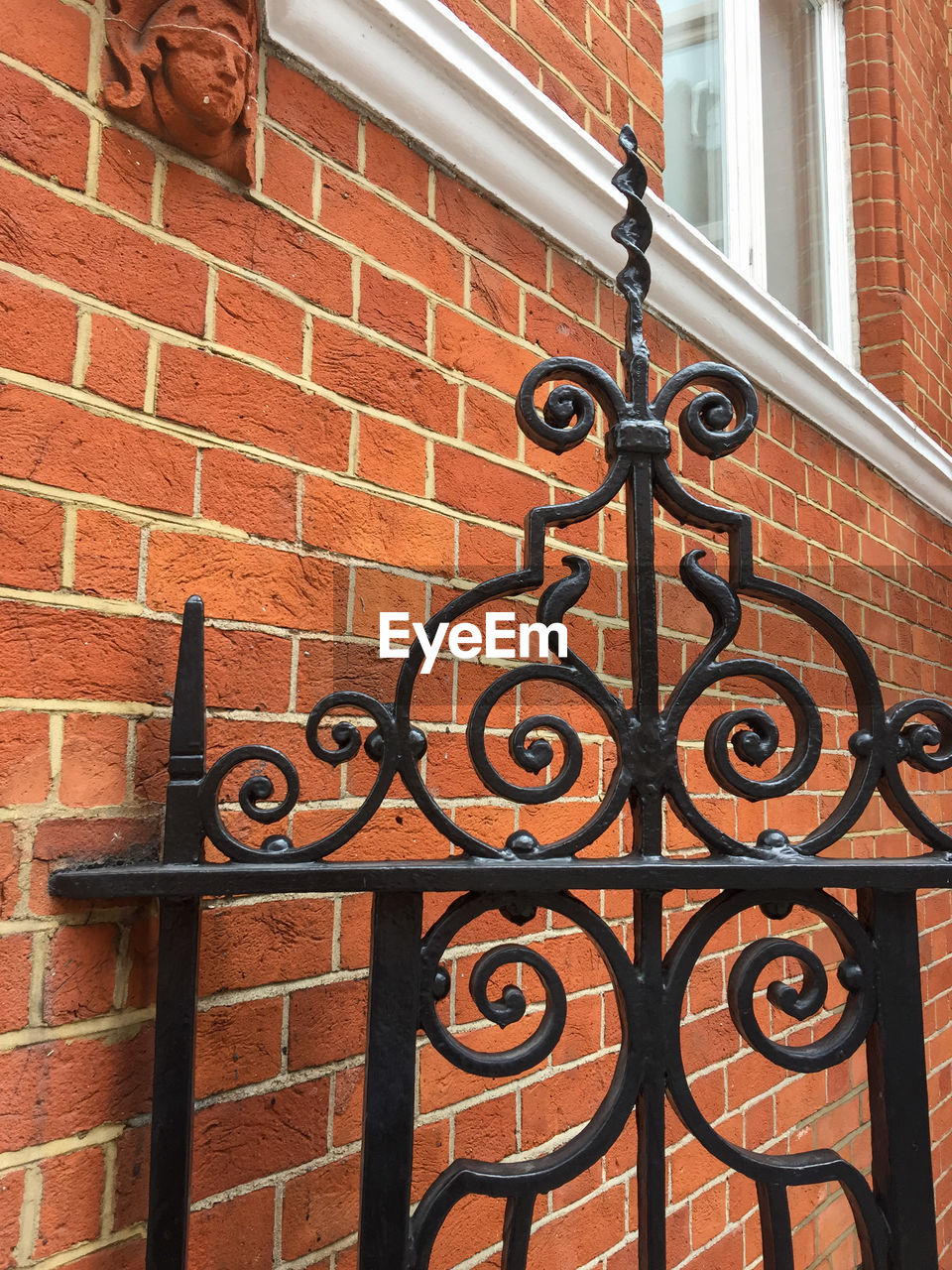 wrought iron, metal, gate, brick wall, building exterior, house, security, architecture, built structure, close-up, outdoors, no people, day, brown, window, low angle view, residential building, cast iron