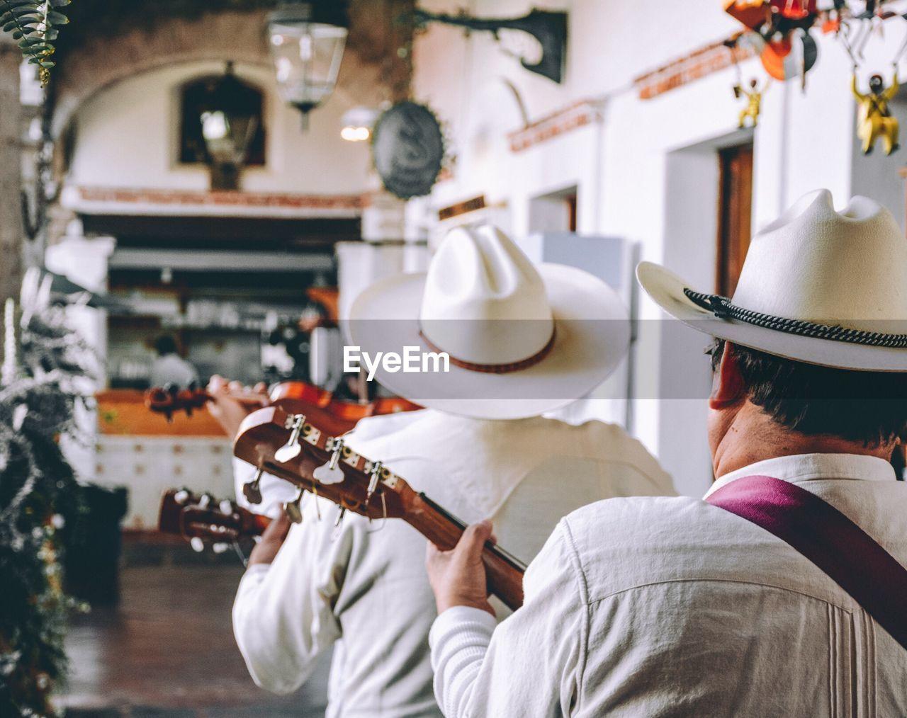 Rear View Of Men Playing Guitars