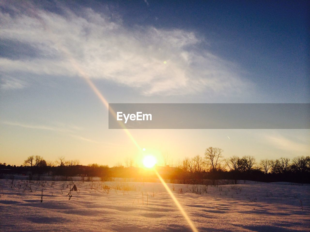 View of snowy landscape at sunset