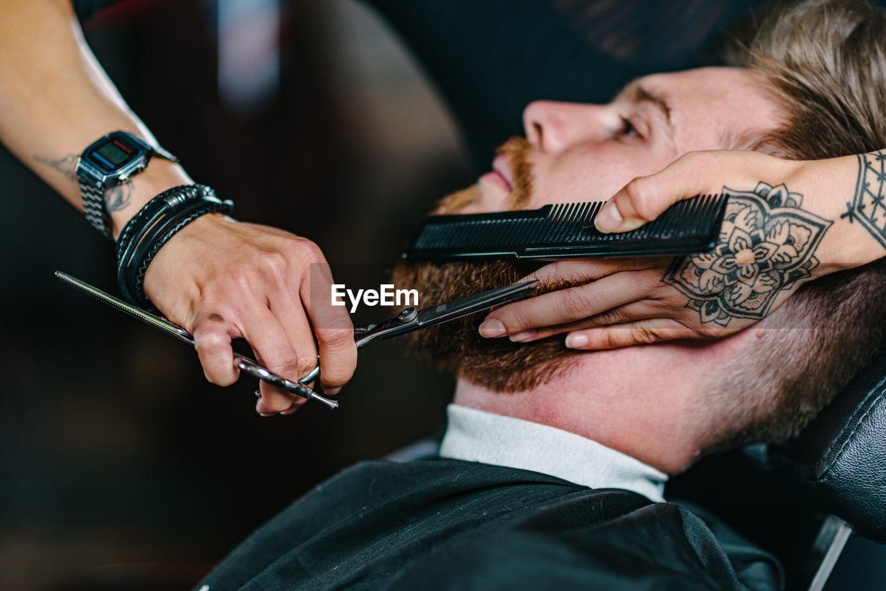 Close-up of woman shaving man beard