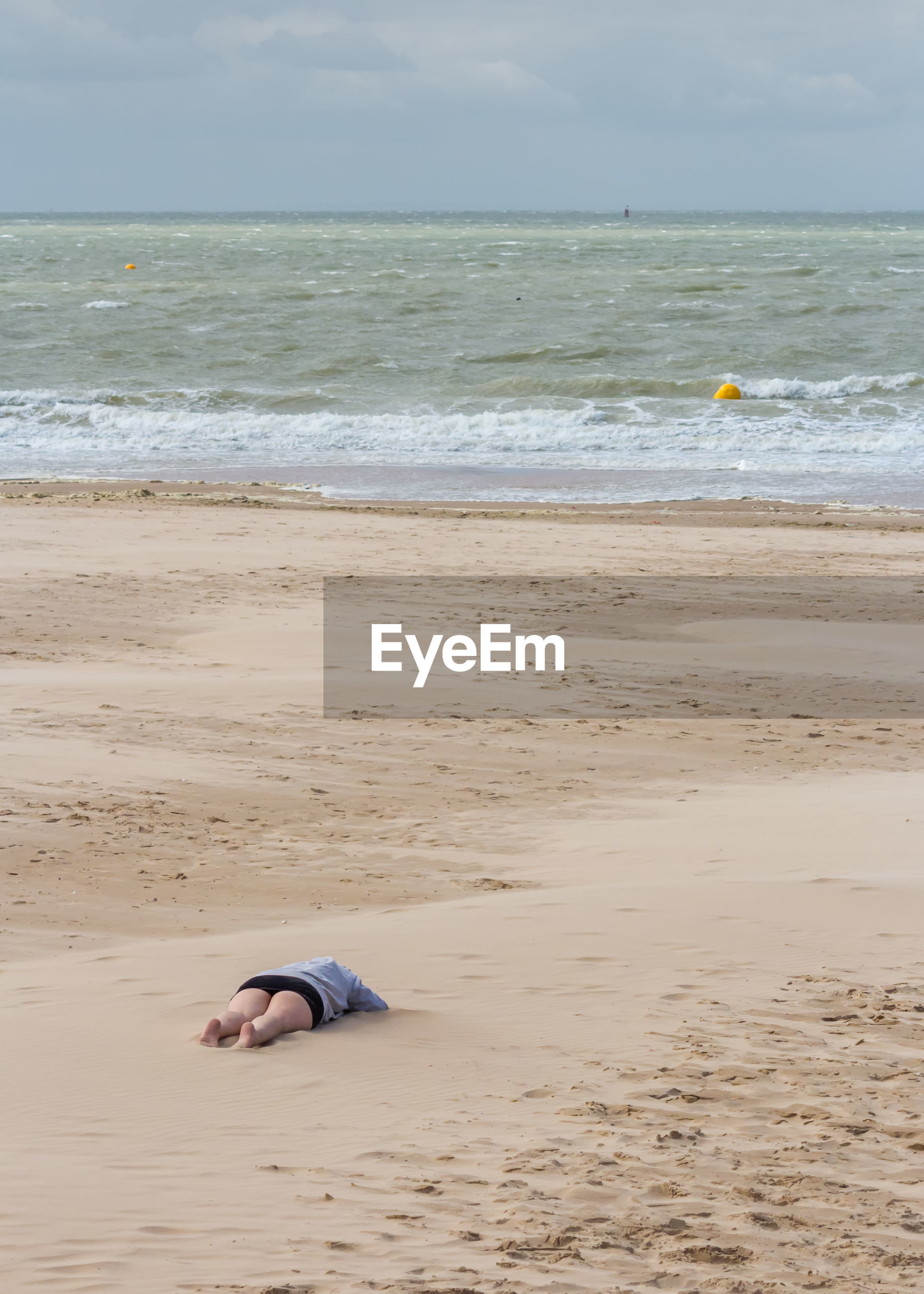 Low section of woman lying down on sand at beach