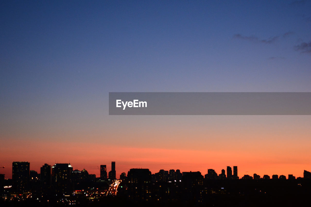 Illuminated Cityscape Against Clear Sky During Sunset