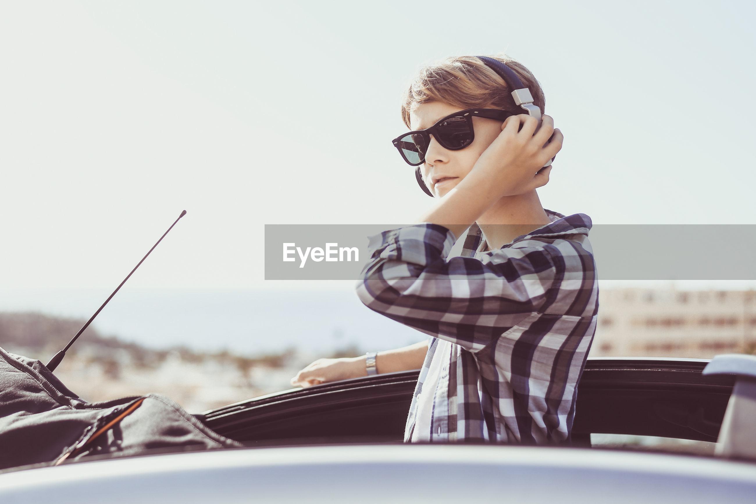 Boy wearing sunglasses against sky