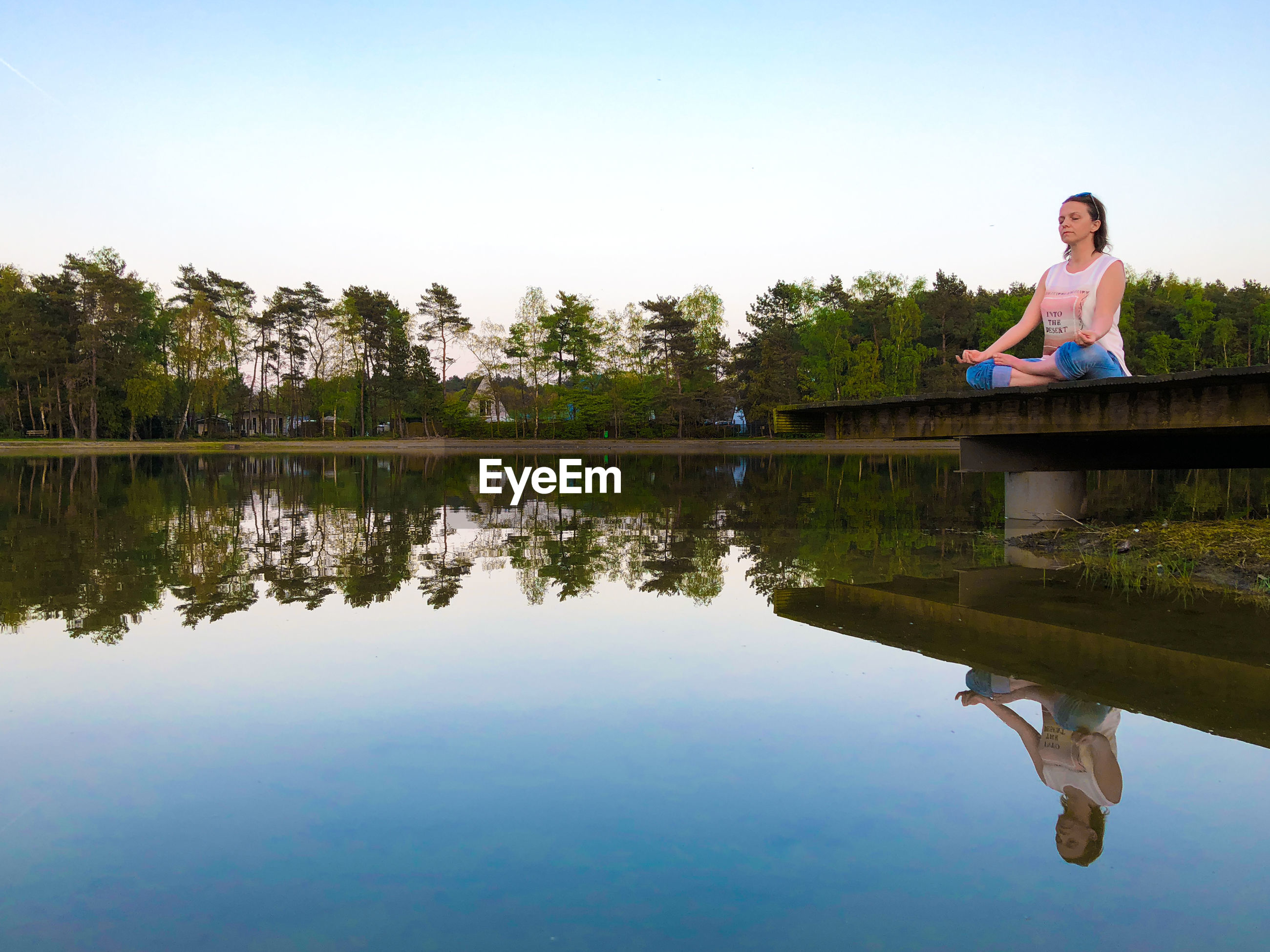 Woman doing yoga while sitting on pier over lake