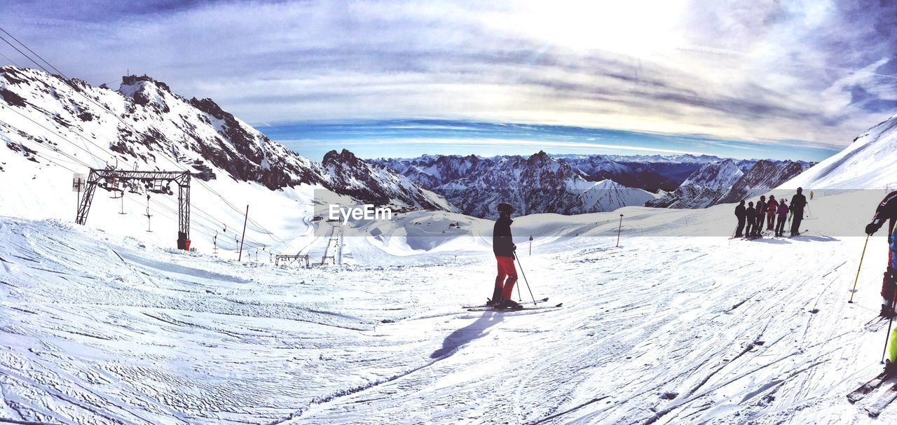snow, winter, cold temperature, weather, nature, beauty in nature, leisure activity, adventure, mountain, real people, sky, snowcapped mountain, scenics, white color, lifestyles, skiing, vacations, sunlight, day, tranquil scene, frozen, cloud - sky, tranquility, outdoors, ski holiday, large group of people, sport, mountain range, landscape, men, extreme sports, ski lift, people