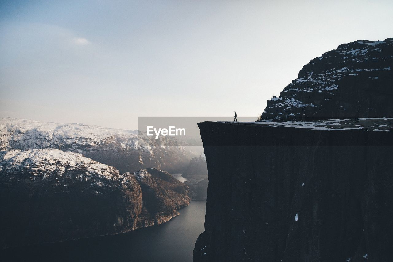 Man On Cliff By River Against Sky During Winter