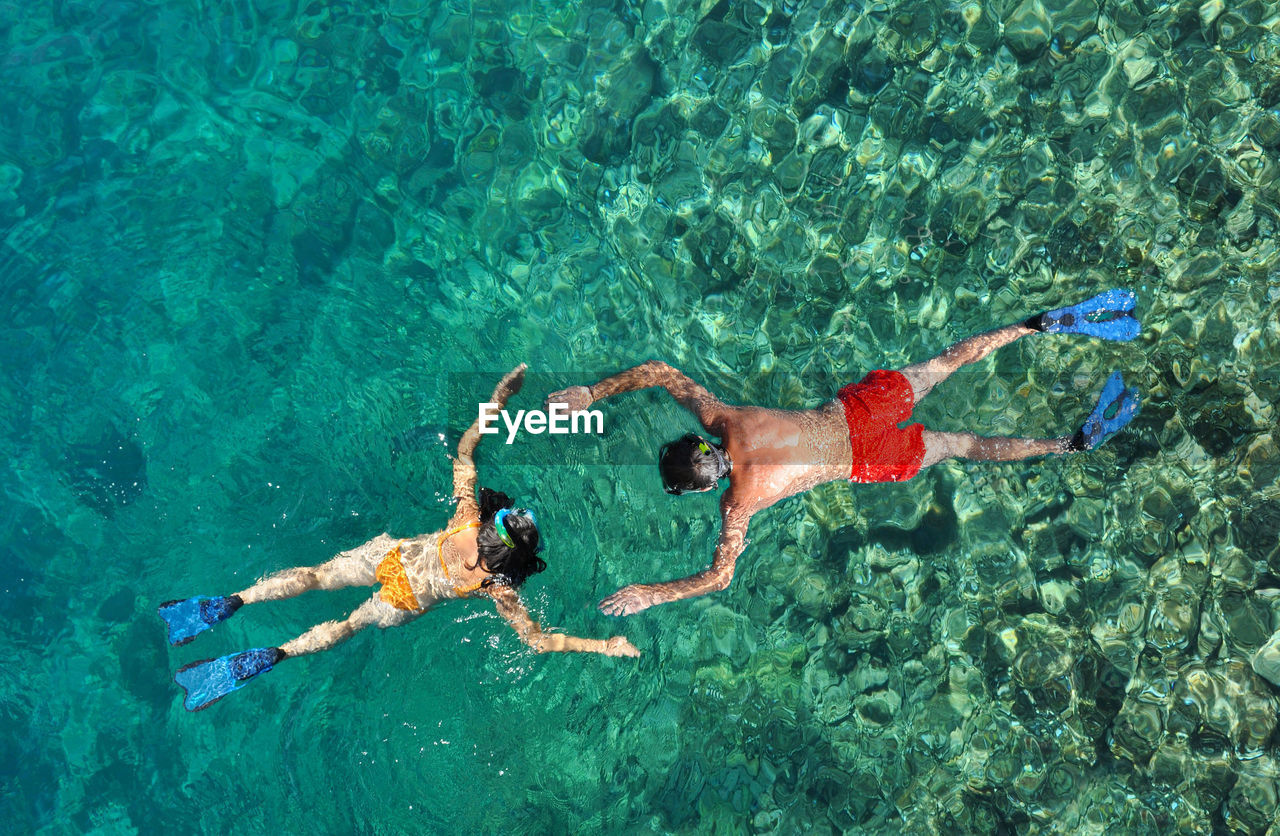 High angle view of men and woman swimming in sea