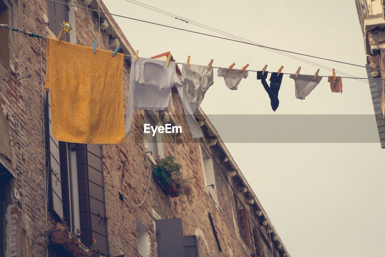 Low Angle View Of Clothes Hanging From String Amidst Buildings